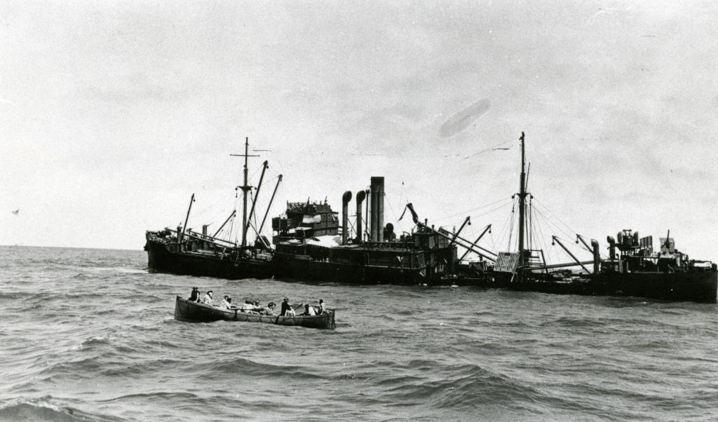 The merchant ship, Macumba, after it was hit. Many survivors were saved via life boats (foreground).