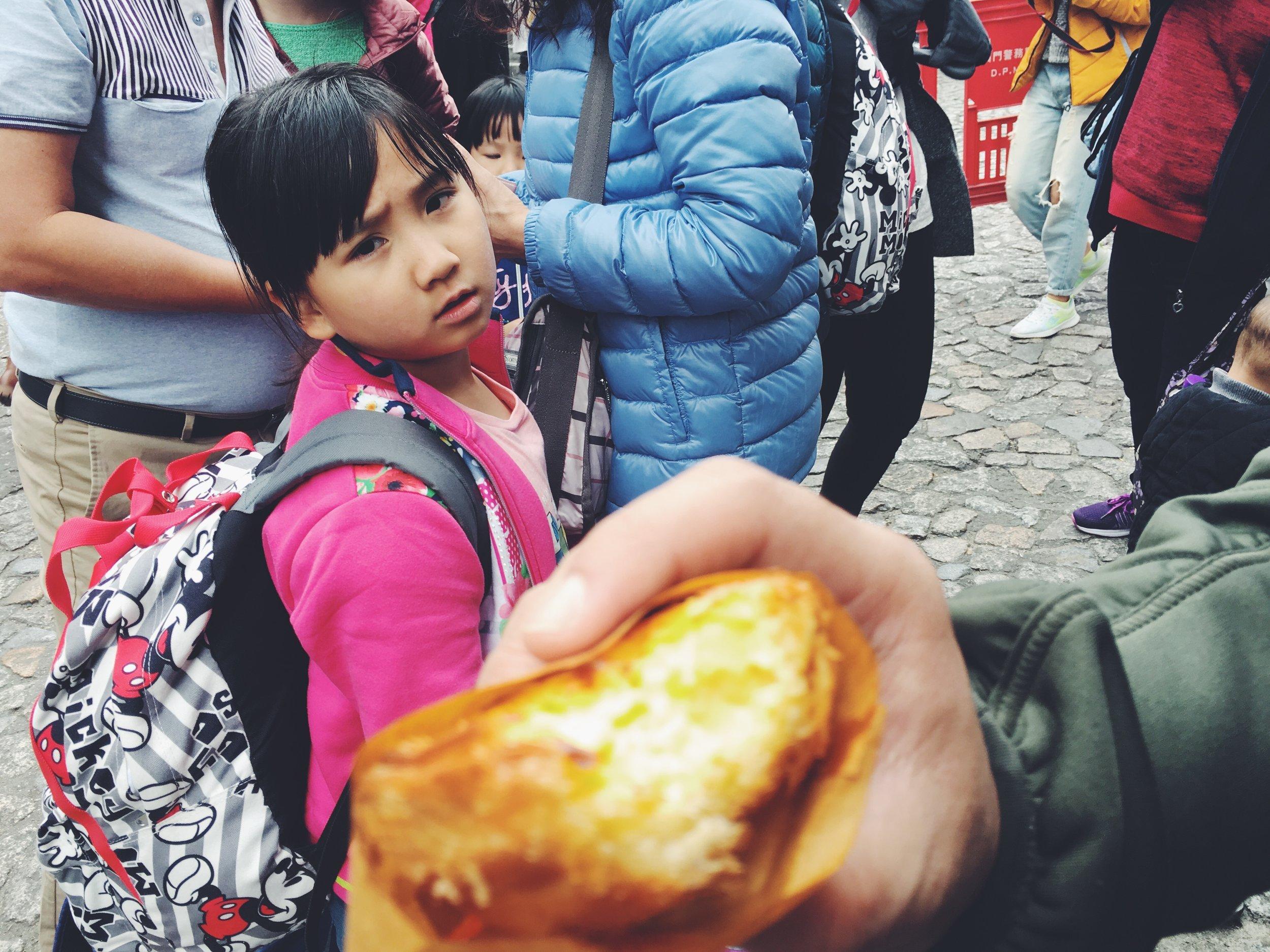Little Girl Staring Longingly at Egg Tart