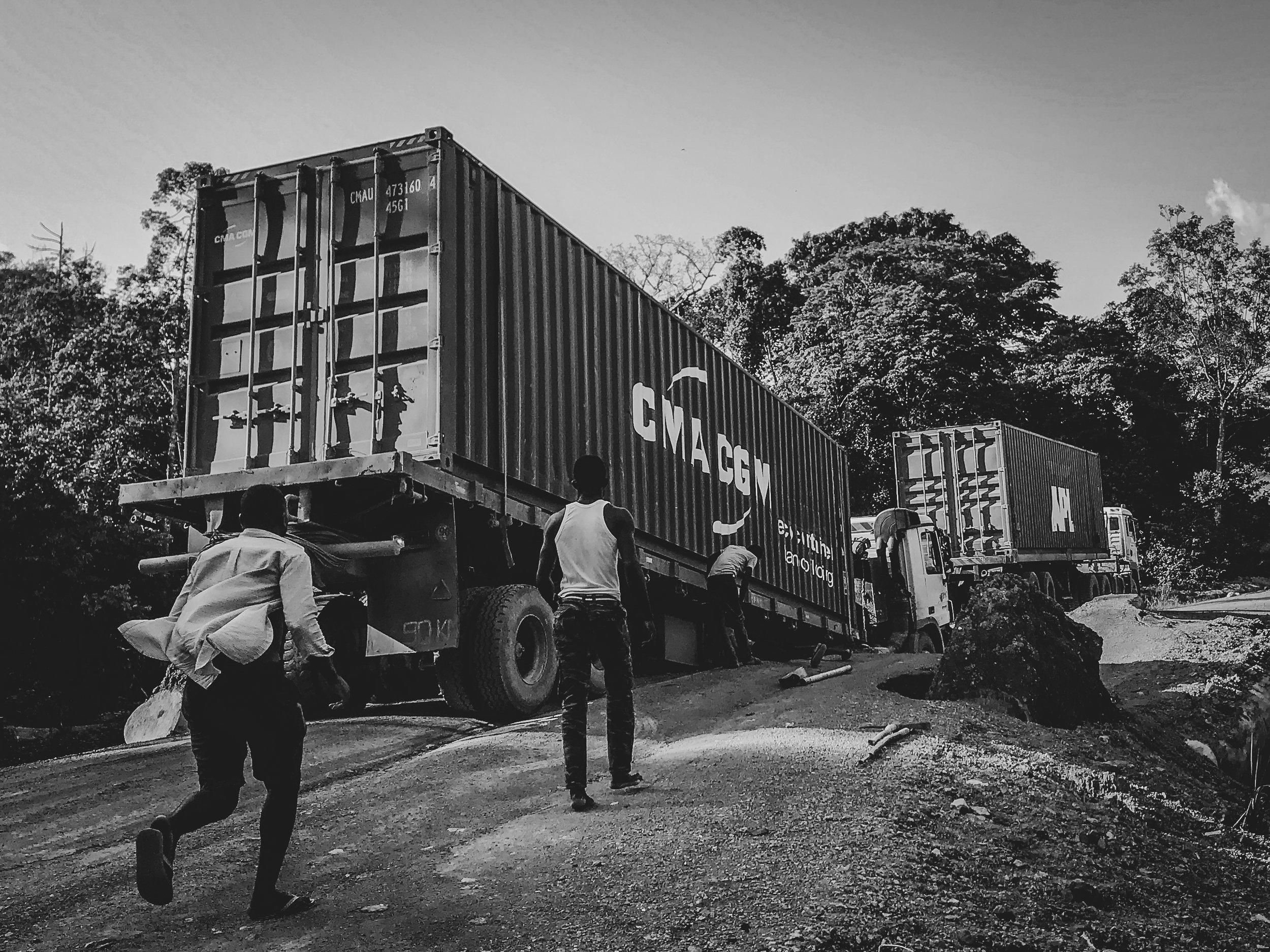 Trucks on collapsed bridge in Mikongo