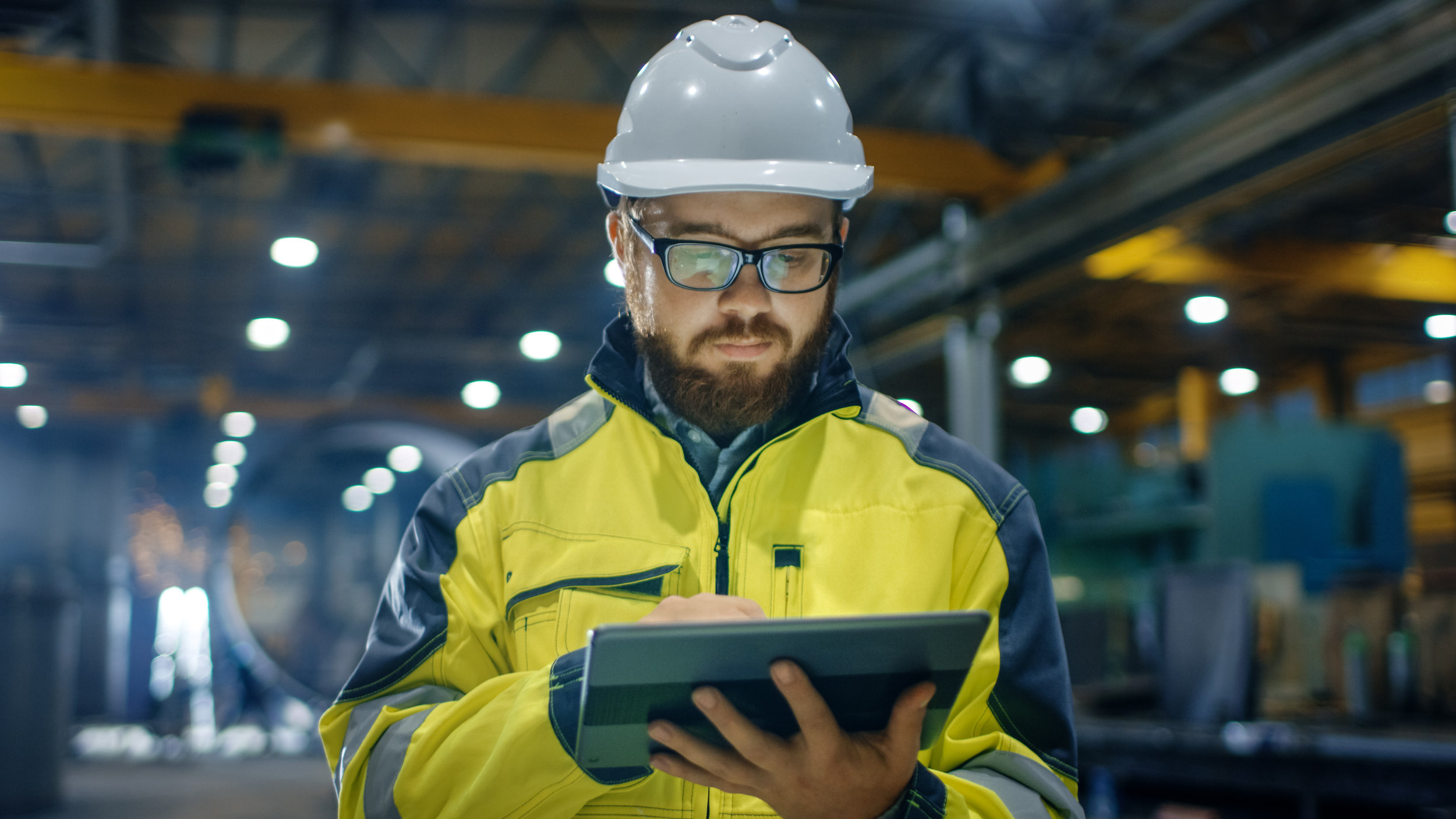 Man wearing hardhat uses construction mobile form on tablet