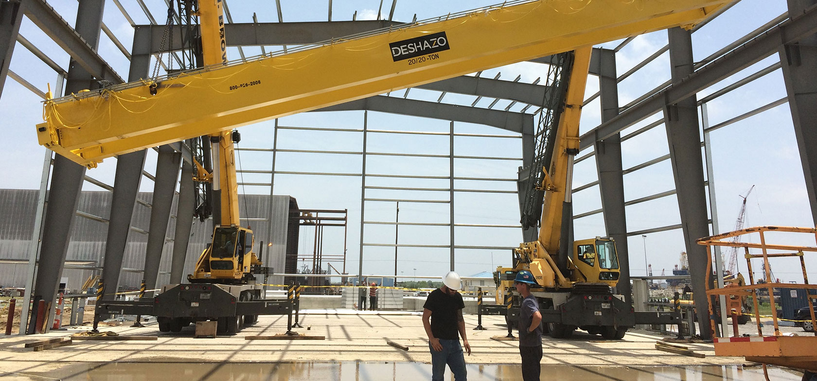 DESHAZO crane manufacturers work on job site with yellow bridge crane