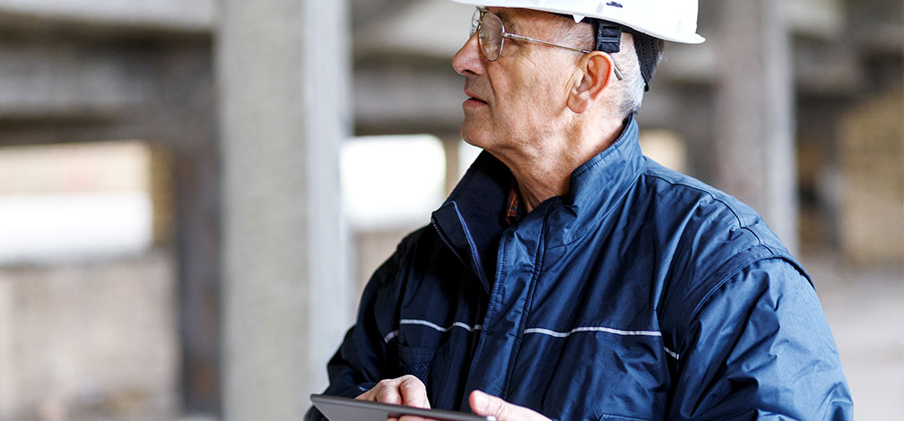 Oldcastle engineer inspects quality control process with white hard hat and ipad
