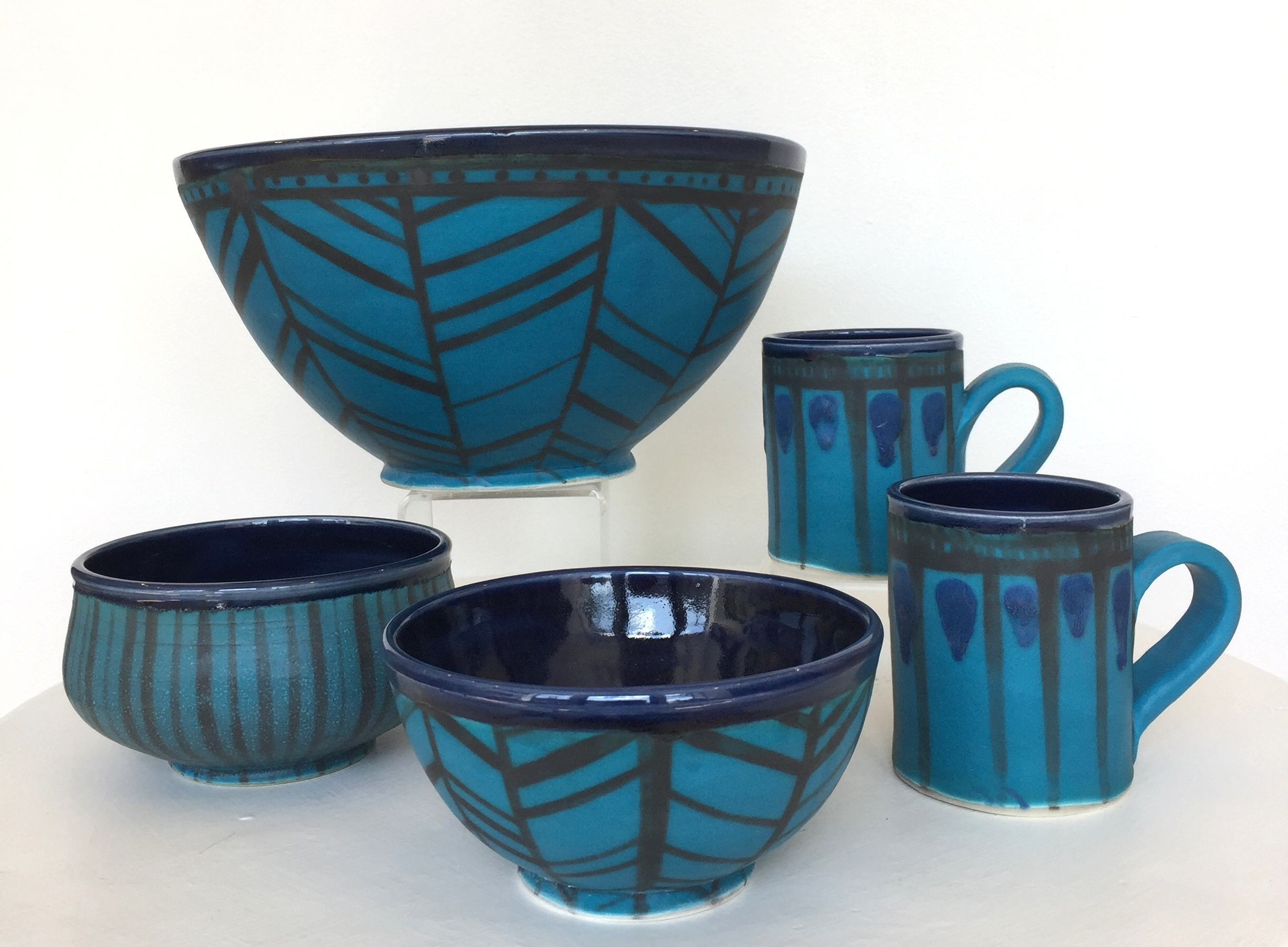 Ceramic bowls and mugs with turquoise exterior and navy interior, herringbone, stripe, and abstract patterns, $38-$150