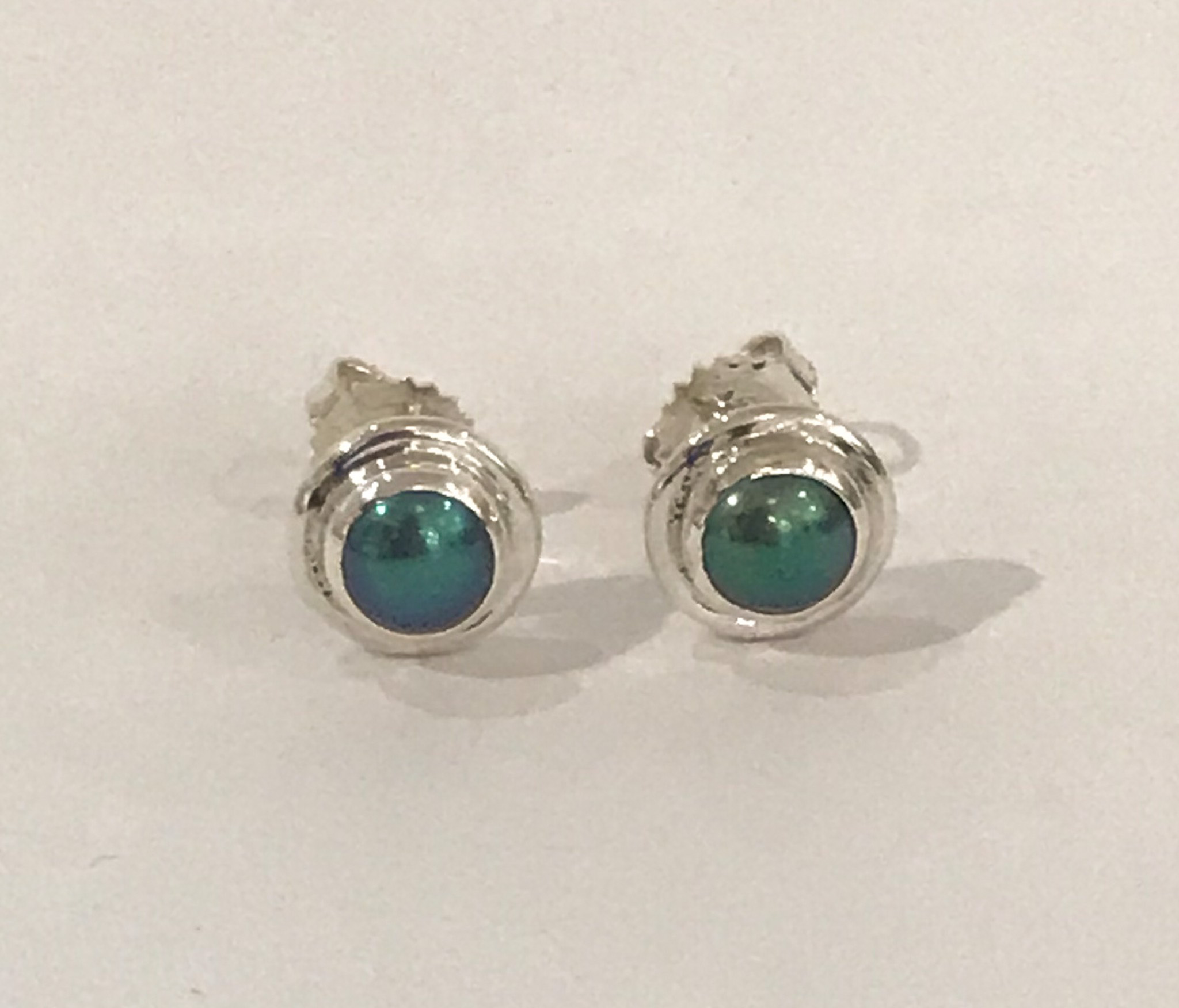 Sterling silver stud earrings set with blue/green freshwater pearls, $80