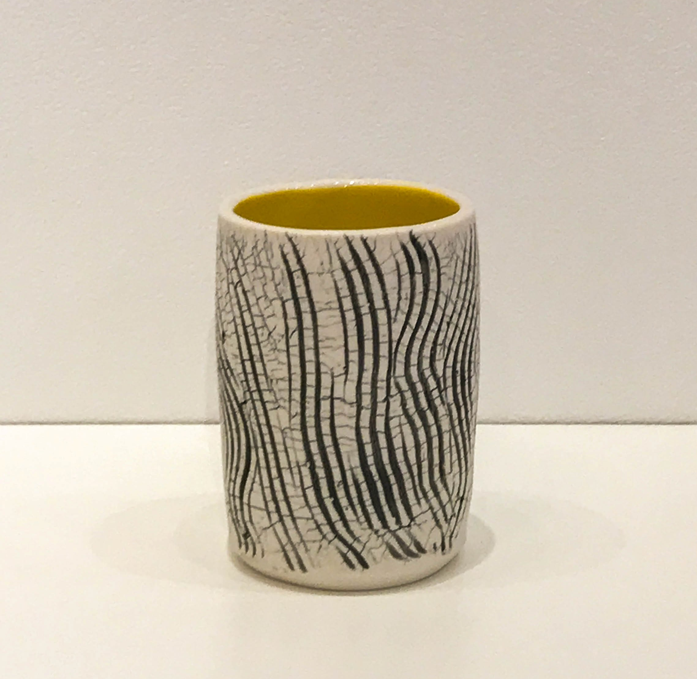 "Wheel-thrown and hand-altered tumbler with black crackle and yellow glazed interior, 4 1/4"" x 3"" x 3"", sold"