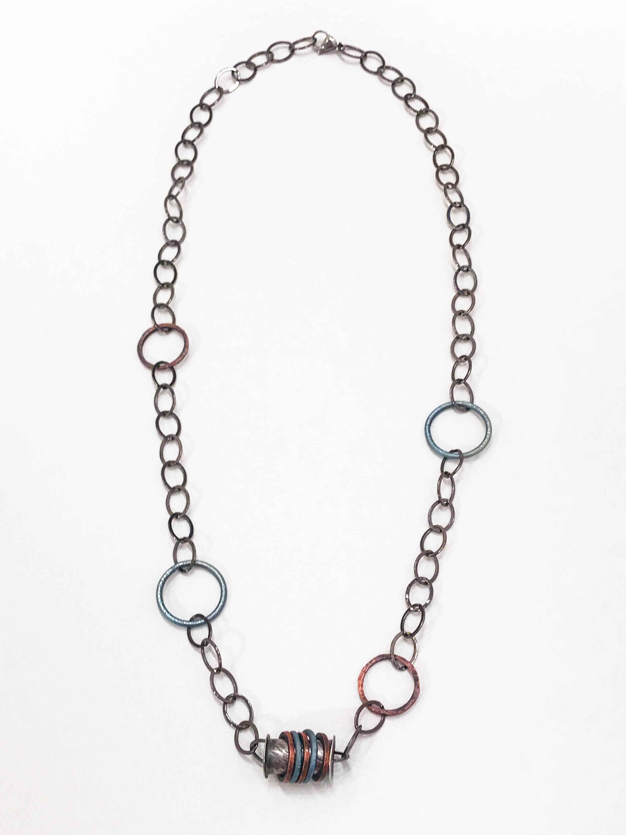 "Necklace with sterling silver, titanium, and copper centerpiece, on titanium, copper, and steel ring chain; 13 1/2"", $120"