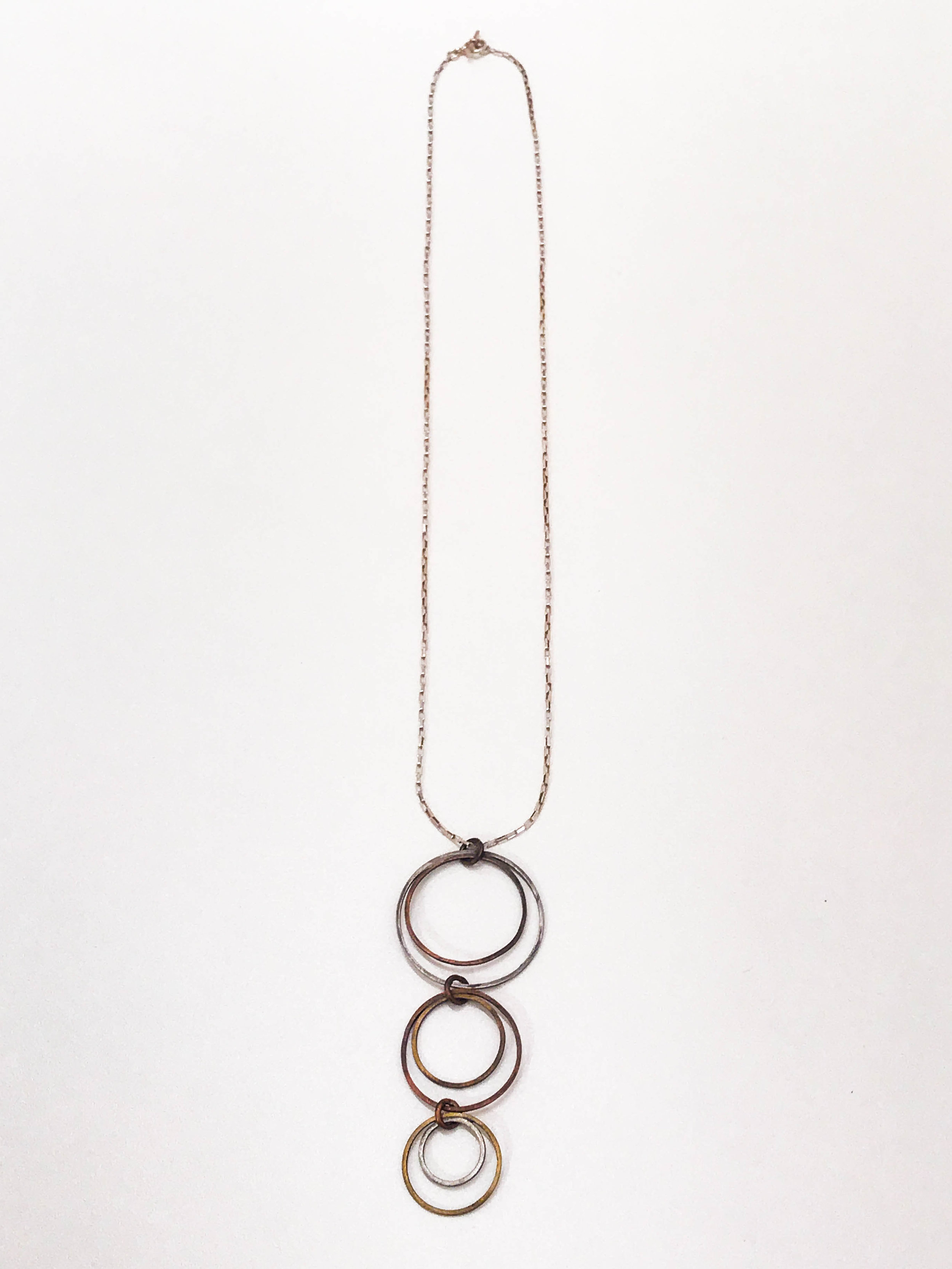 "Sterling silver chain with pendant of 6 interconnected circles in sterling silver, copper, and brass, pendant dimensions 3 1/4"" x 1 1/4"", $90"