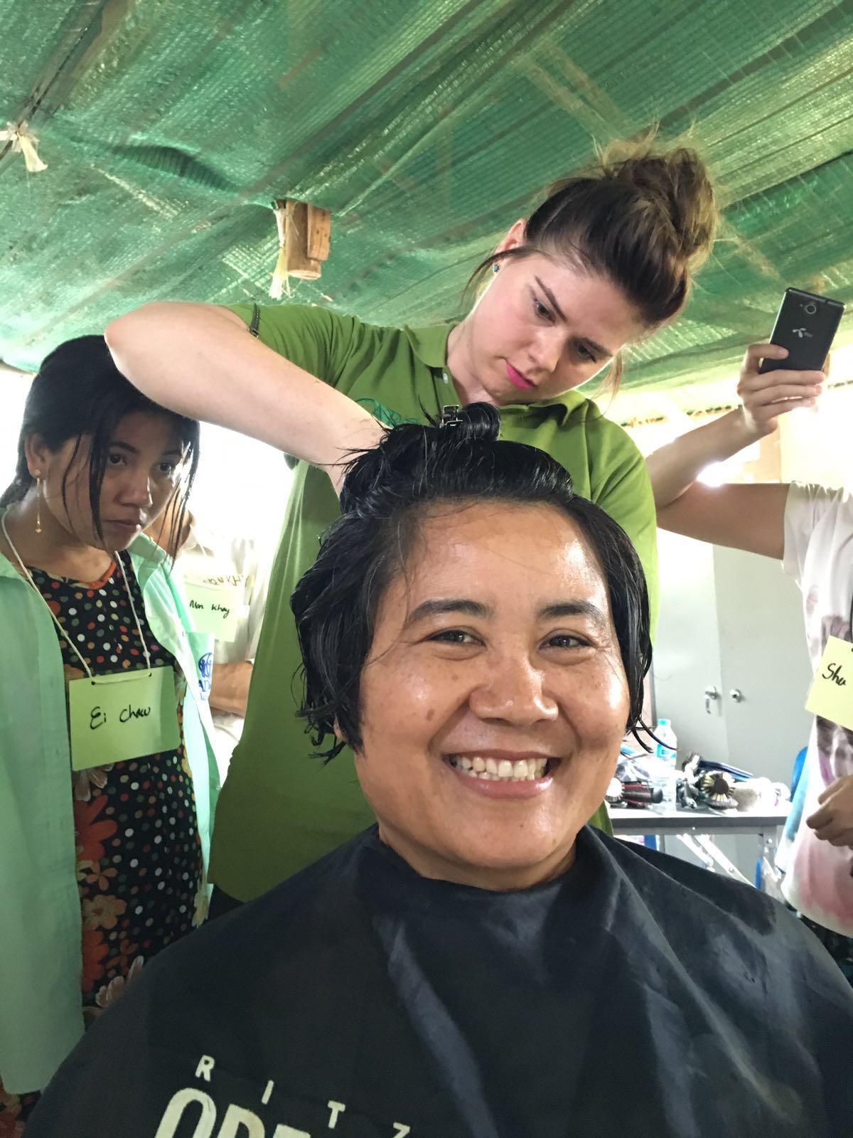 Natalie Hansen from HAUS Salon demonstrates hair cutting techniques on Dina, GBV Manager for Nu Po.
