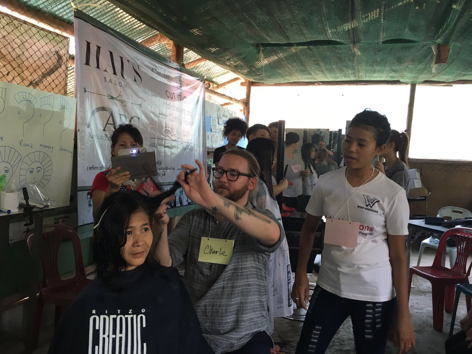 Students watch while Charlie demonstrates a new style for Thi Dar Aung.