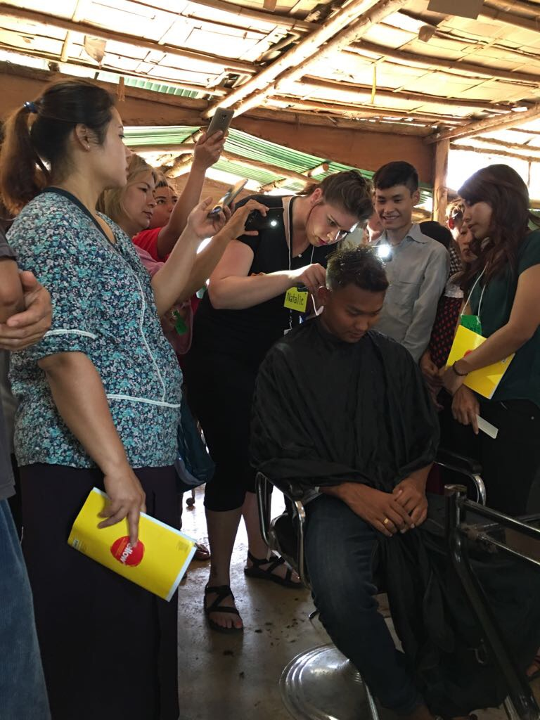 Natalie demonstrates a men's haircut as students watch closely.