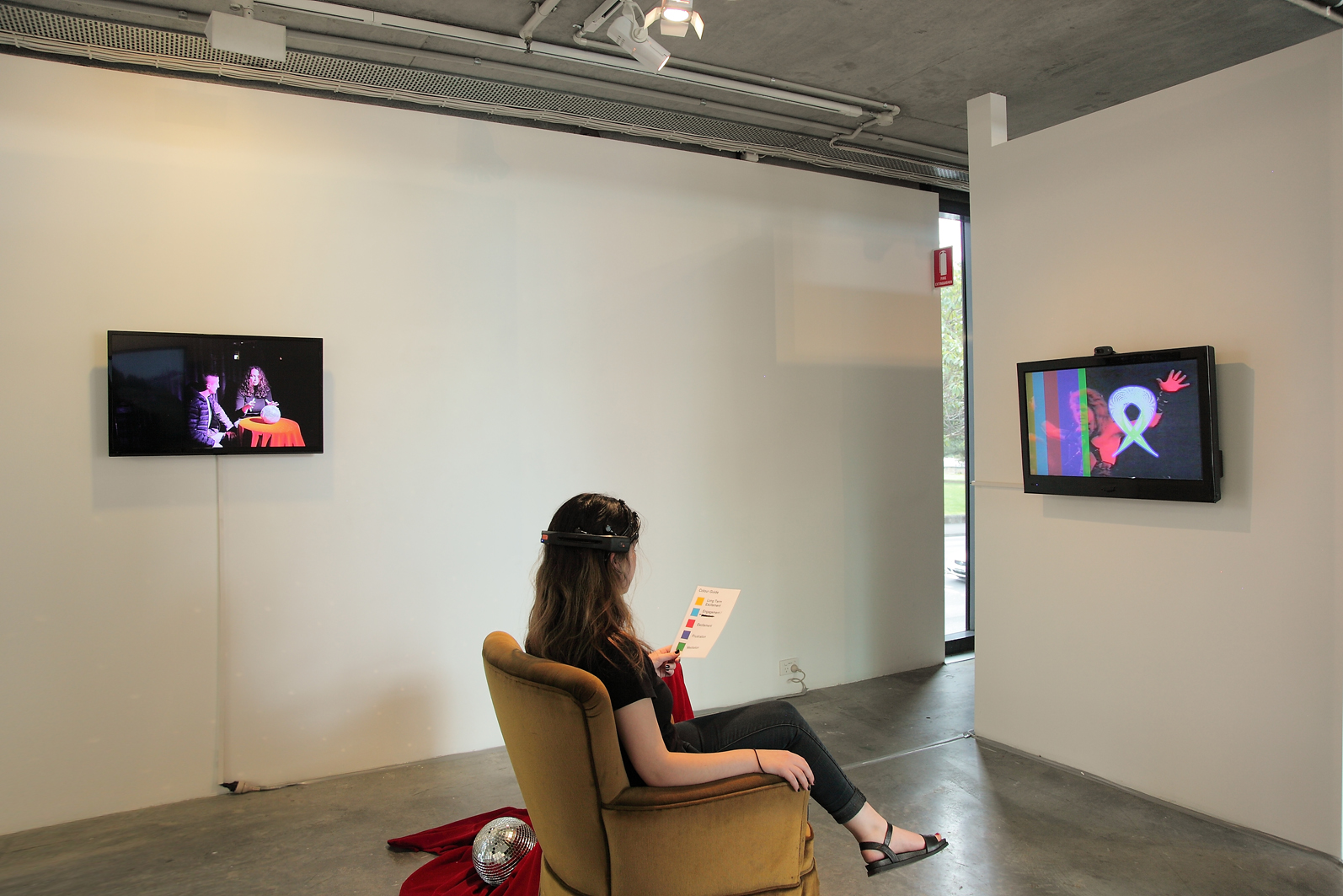 Jacquelene Drinkall,  Visual Telepathies  exhibition installation view at Verge Gallery, 2015, showing two artworks. LEFT/CENTRE: Jacquelene Drinkall, 'Disco Ball Gaze' HD video on HD monitors (colour, audio) disco ball, velvet cloth over small table, documentation of participatory endurance performance at The Cube, Oxford Art Factory, 2014 (no audio was exhibited in the Verge Gallery installation); and Jacquelene Drinkall in collaboration with Warren Armstrong, RIGHT/CENTRE: 'Hypnosis in Video for Brain Computer Interface' velvet chair, EEG neuroheadset and participant interaction, live video camera feed, laminated paper map of mental states correlating to colours visualising brain data, 2015 (my video montage of scenes of hypnosis in video, titled 'Hypnosis in Video', colour, audio, 20 minutes, was made in 2001 and was this year repurposed for EEG neuroheadset interaction)