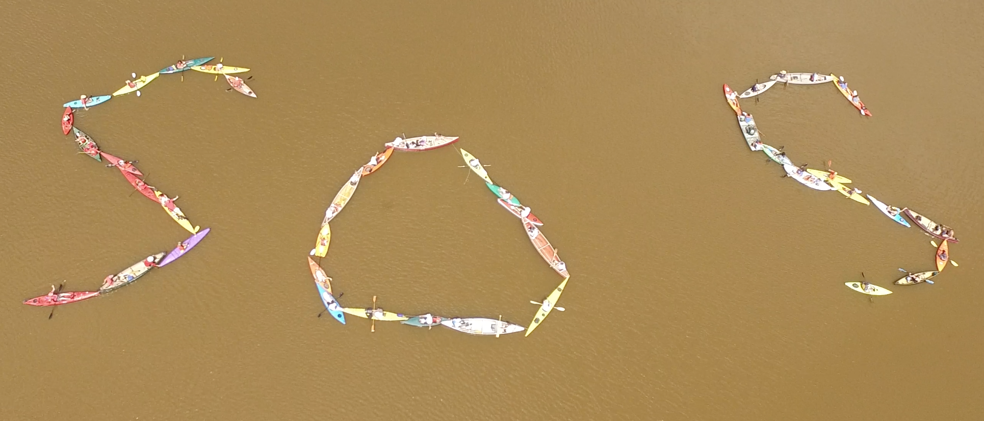 """Sunday, July 29th, 2018 Drone footage by Cody Buesing / ReThink Films  Keith Buesing  conceptualized and organized a live community art exhibition with kayaks and canoes. Together they spelled """"SOS"""" - """"Save Our Sanctuary"""" in an effort to save Tillson Lake."""