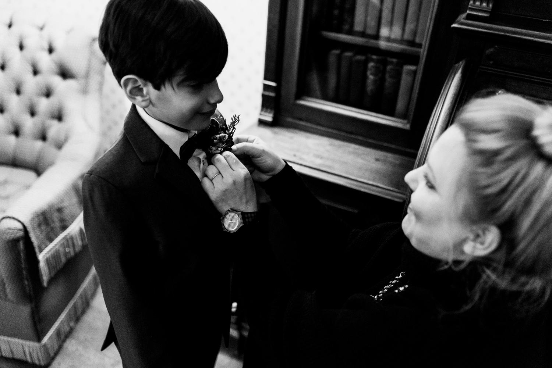 boy putting on boutonniere at wedding