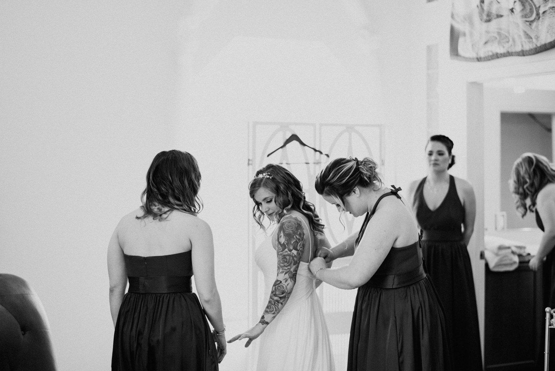bridesmaids helping bride put on her dress