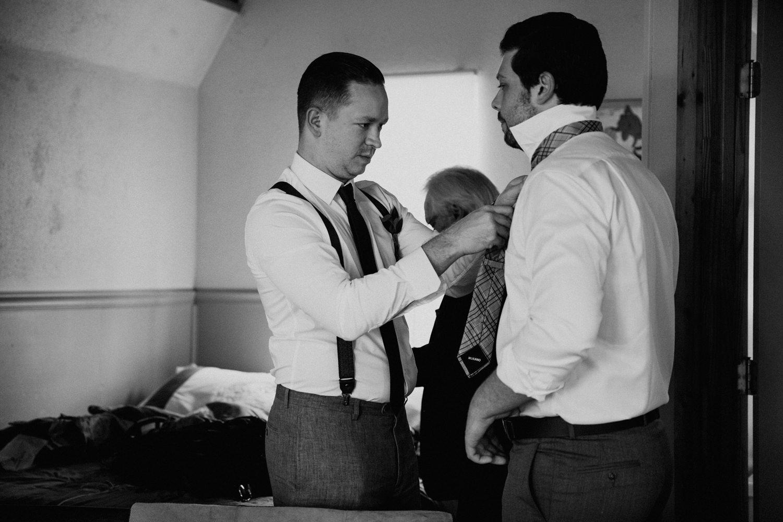 groomsman helps groom tie his tie