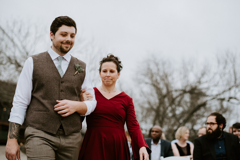 a groom walks his mom down the aisle at Austin wedding