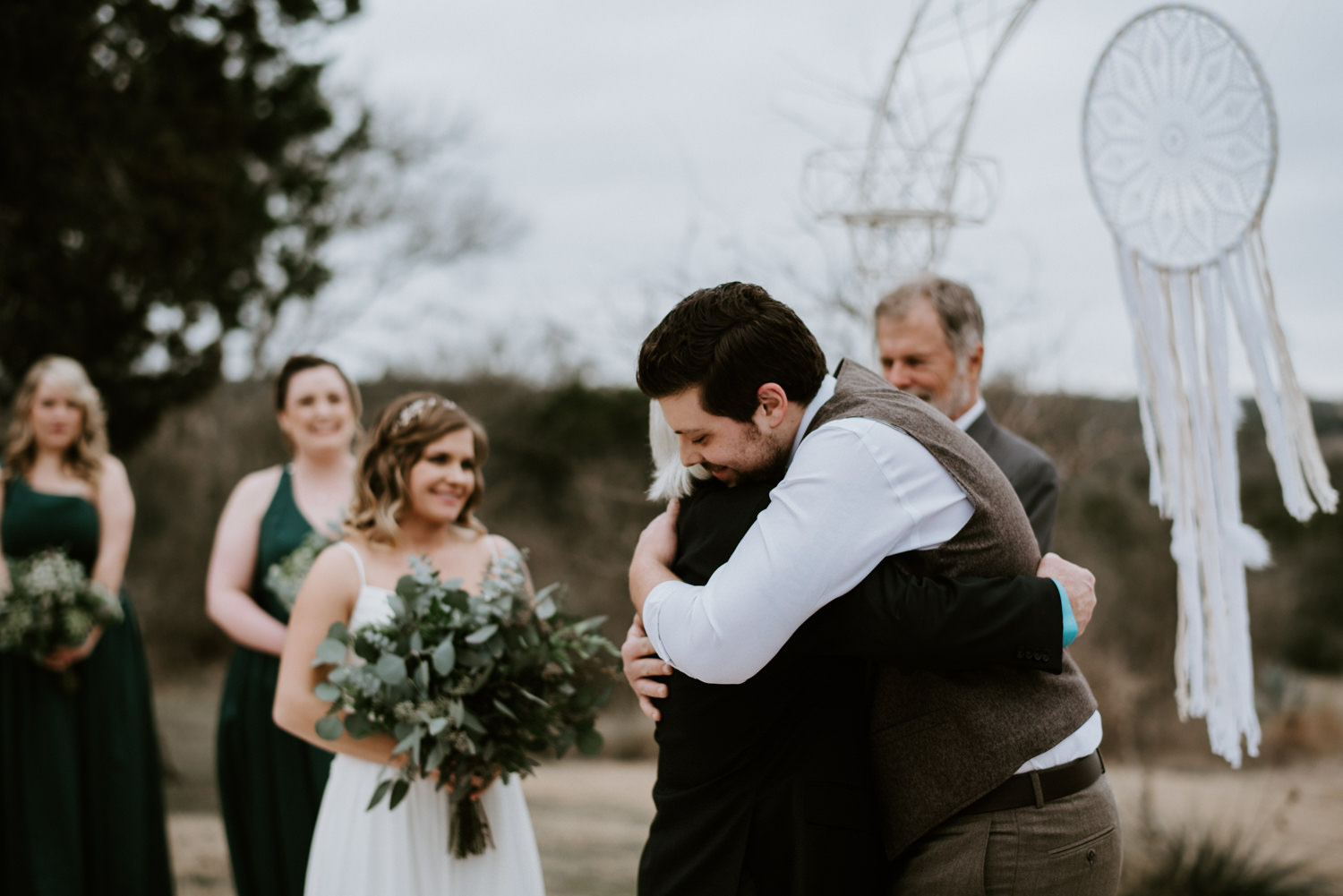 Father of bride and groom hug at the altar