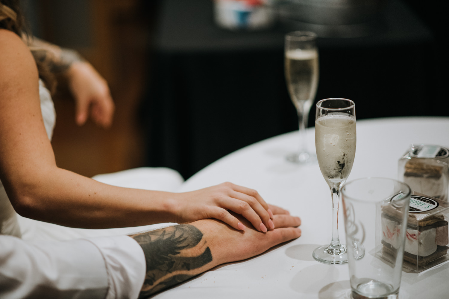 bride and groom hold hands during wedding reception