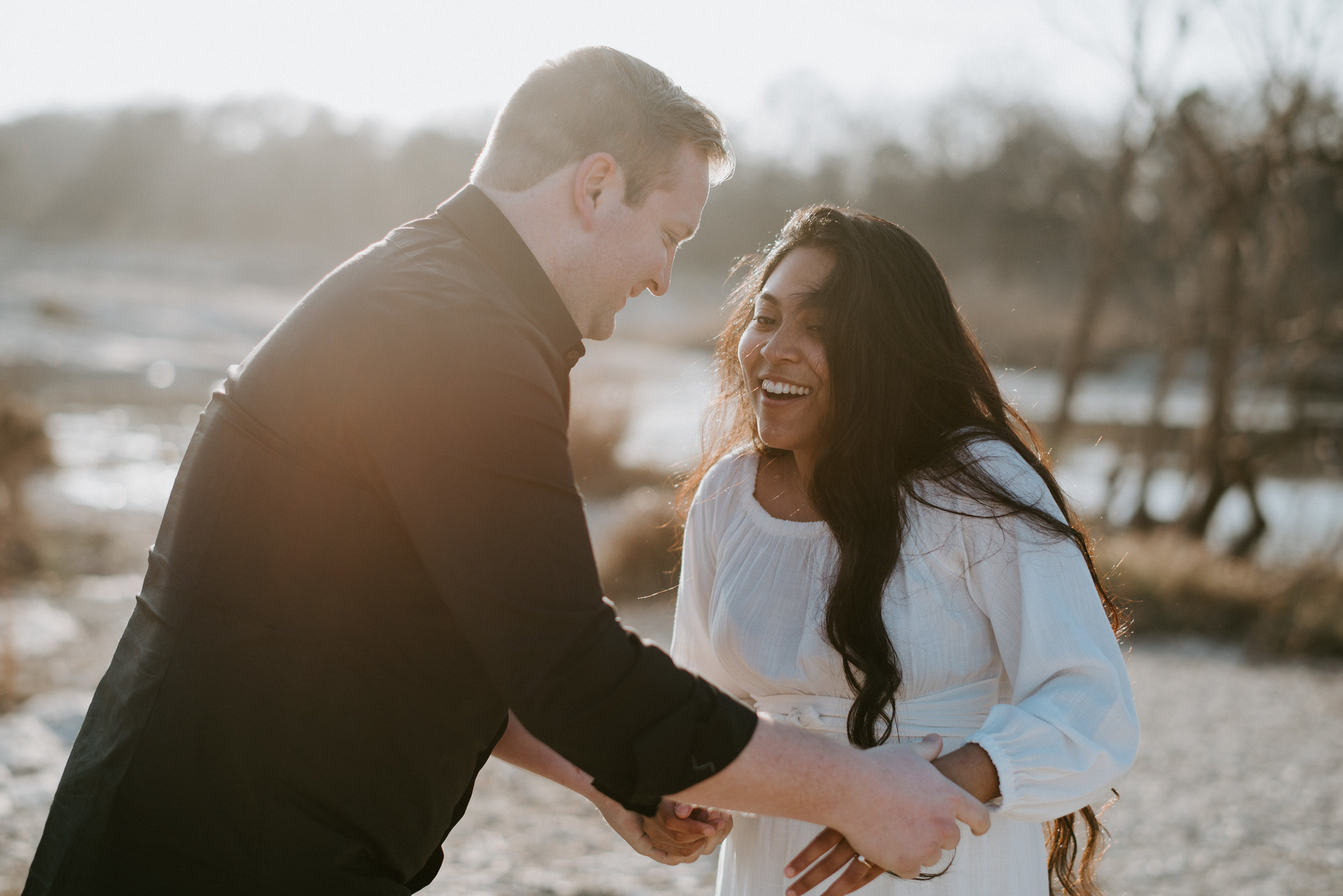 engaged couple laughs during engagement session at mckinney falls