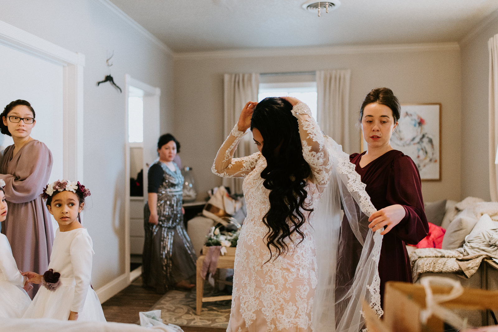 maid of honor puts on brides veil