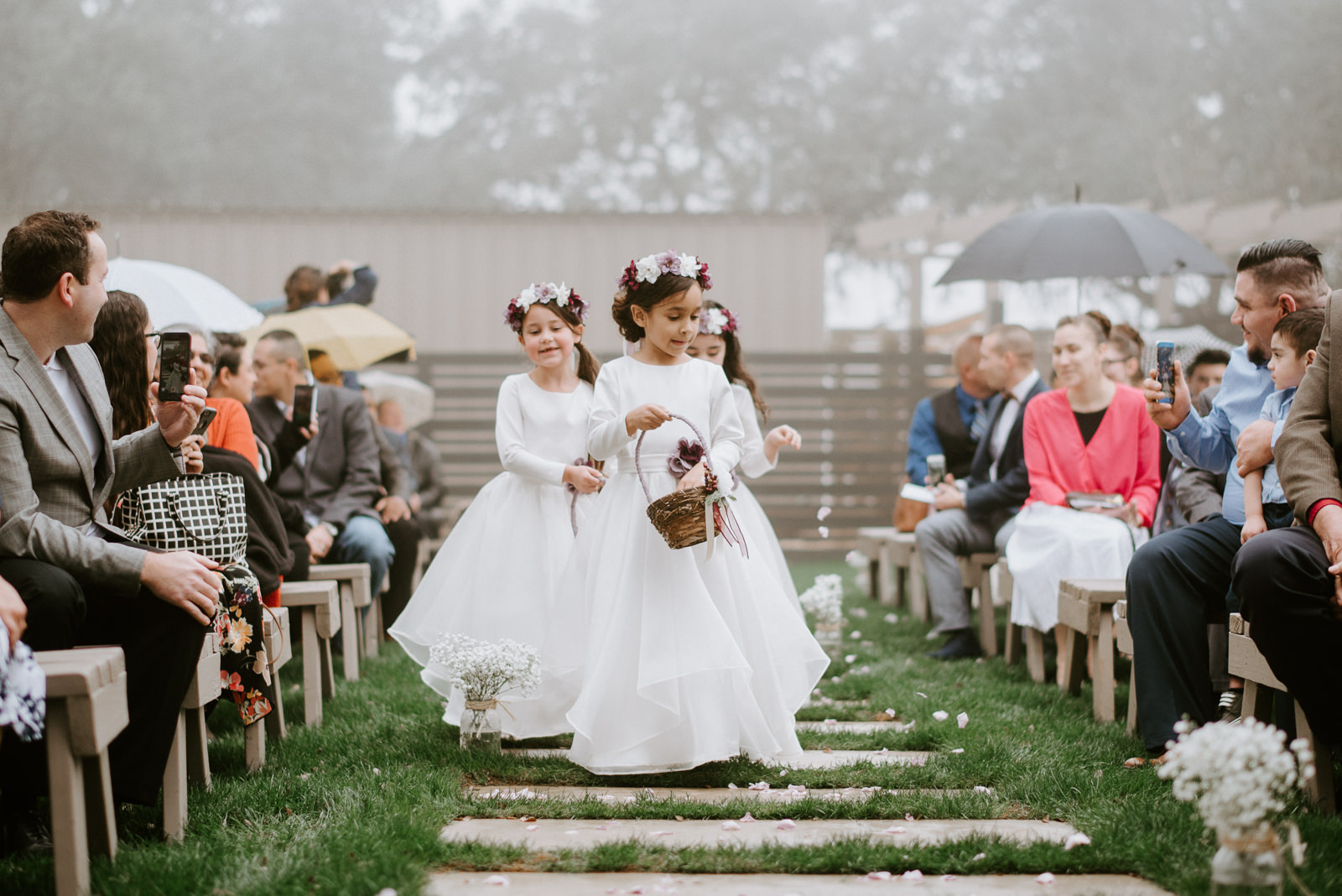 flower girls dance down the aisle before hill country wedding