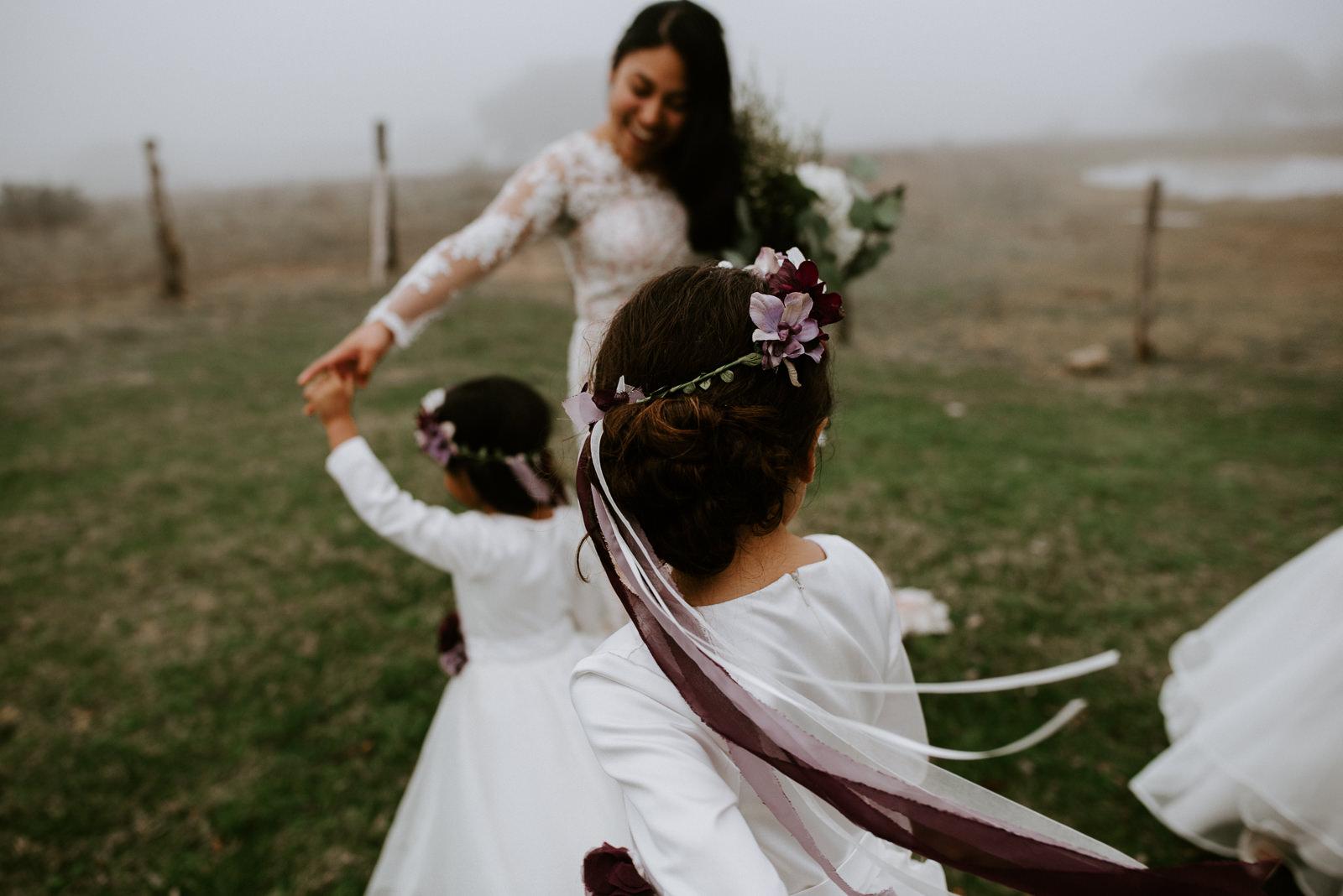 flower girls dance in a field after wedding
