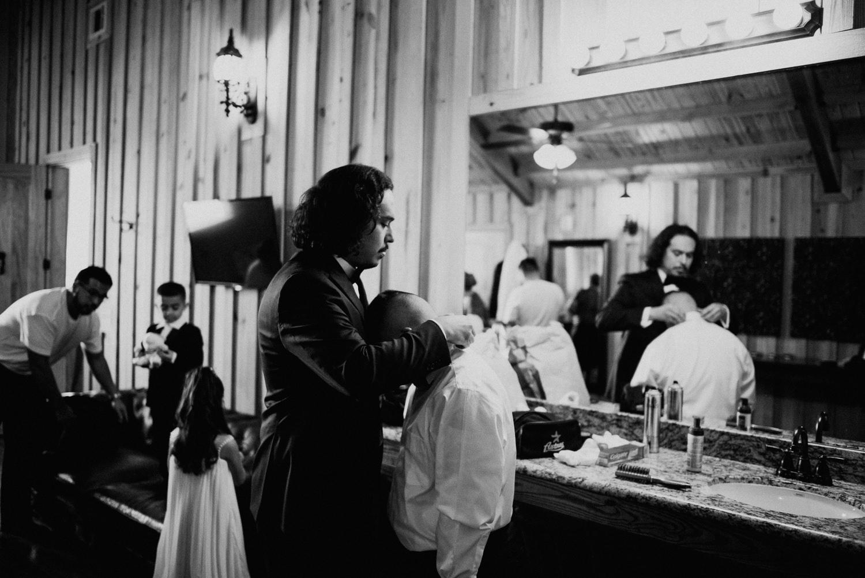 Groom helps tie a necktie before houston wedding