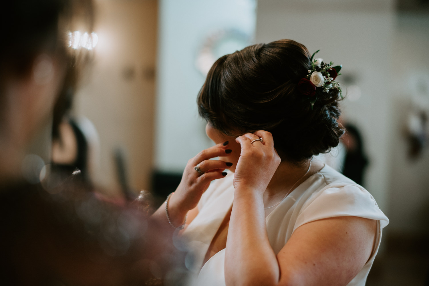 bride puts on earings before her wedding in The Woodlands