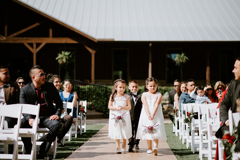Flower girls and ring bearer walk down the aisle