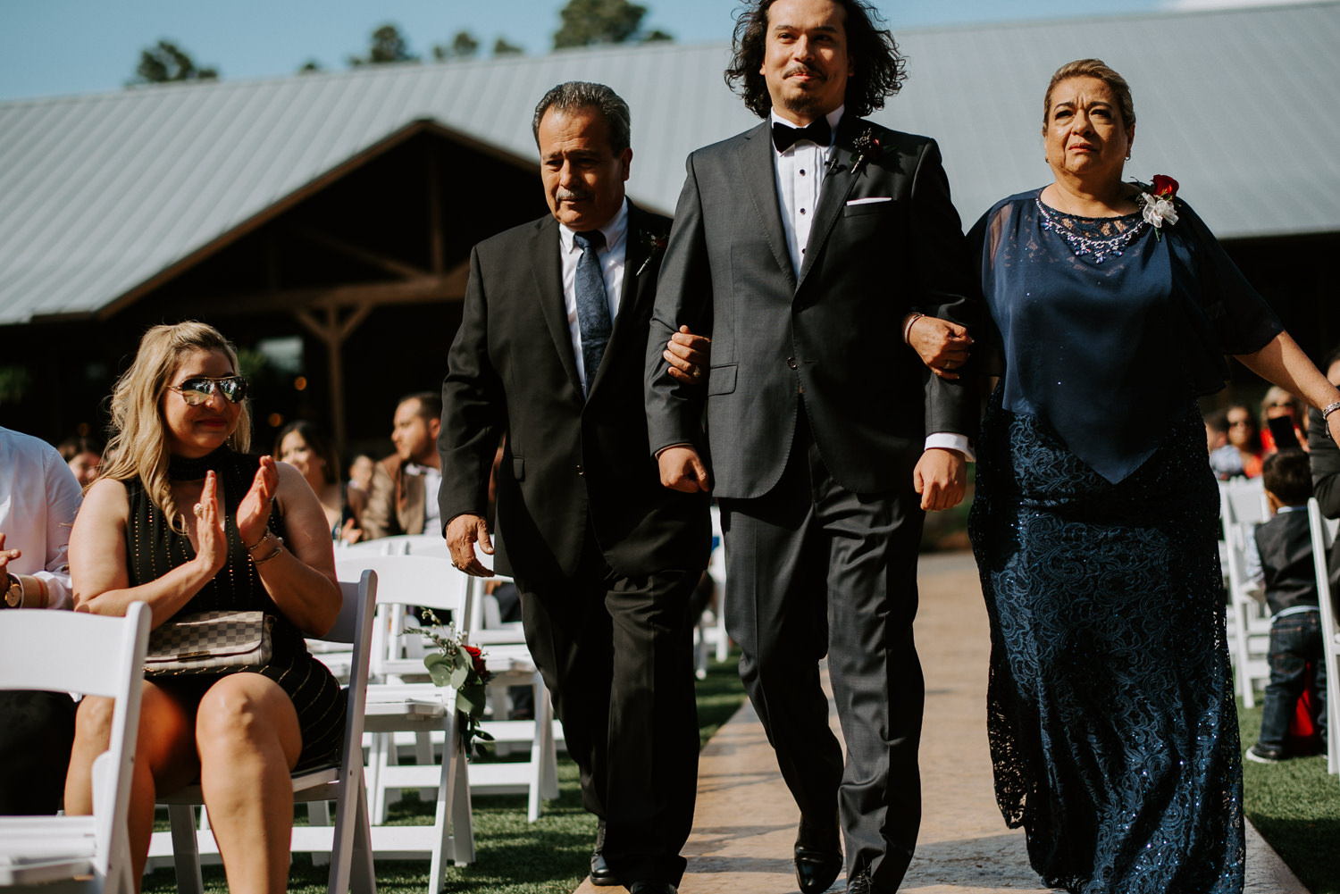 groom and his parents walk down the aisle at The Springs event venue