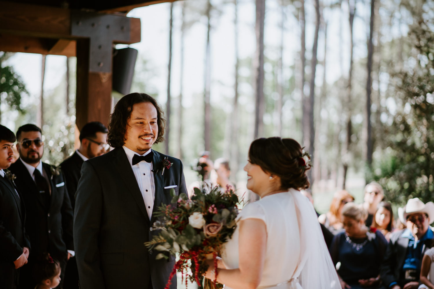 Groom smiles at bride during houston wedding ceremony