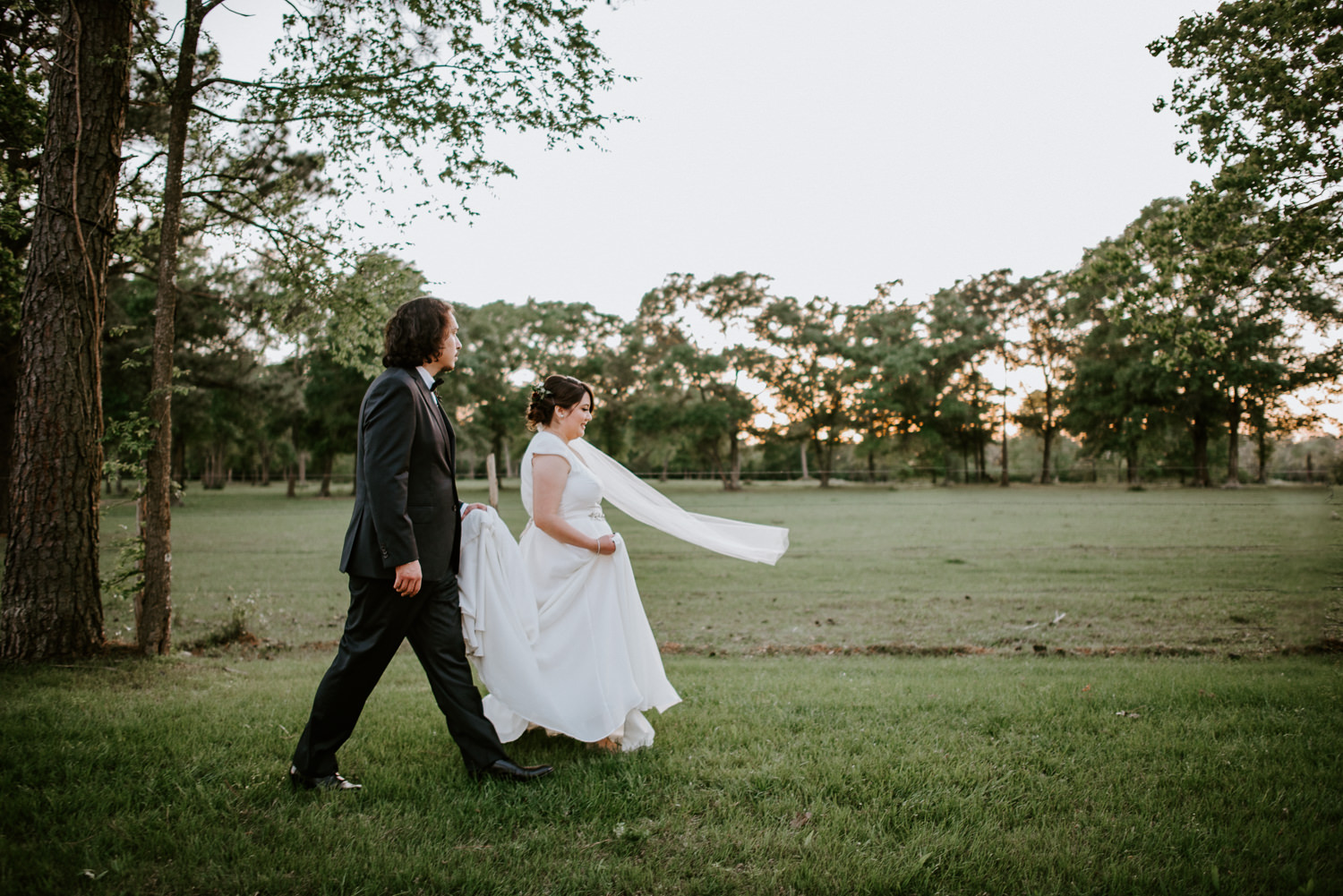 bride and groom walk in a field at texas wedding