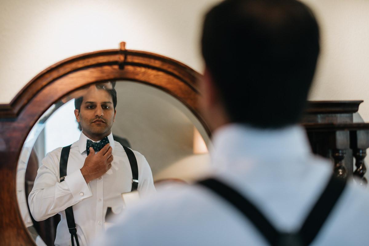 groom fixes bow tie in mirror