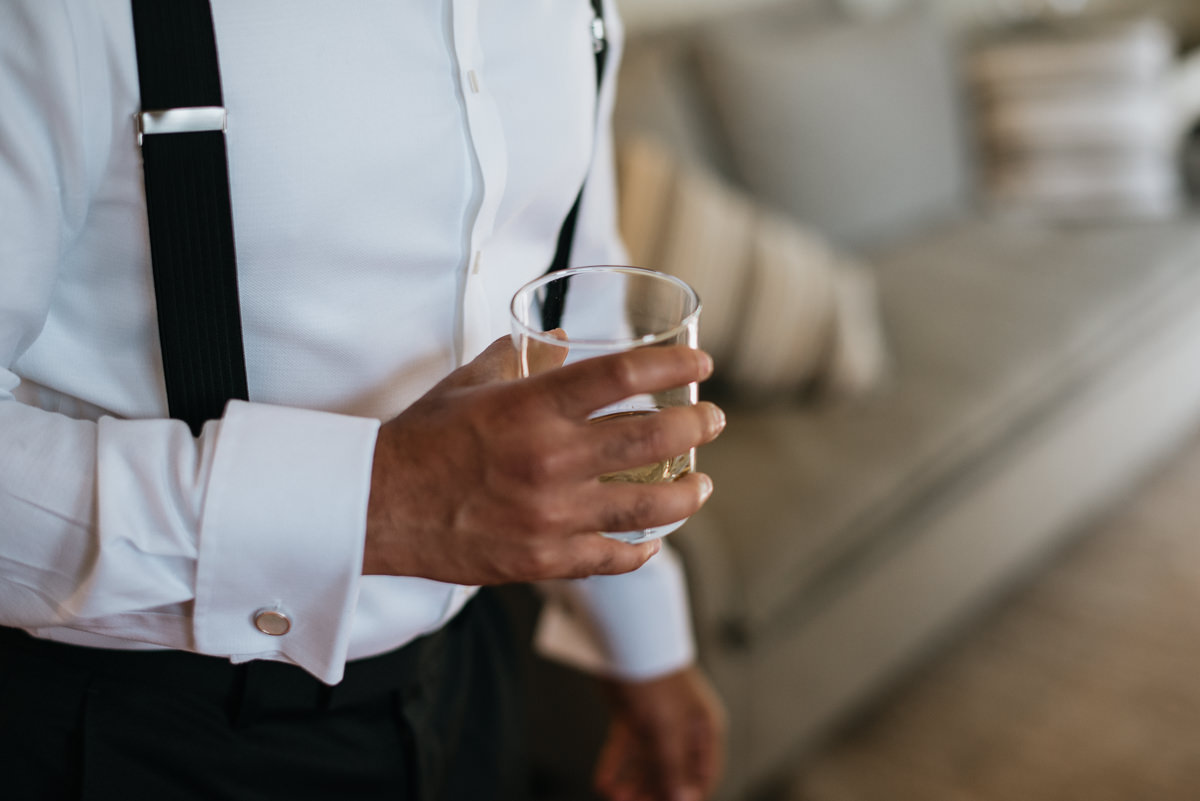 groom holds glass of scotch before his wedding