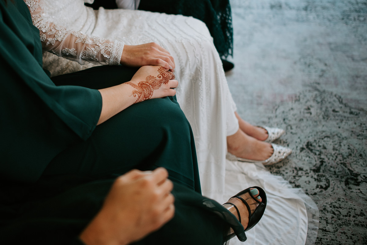 bride and maid of honor hold hands