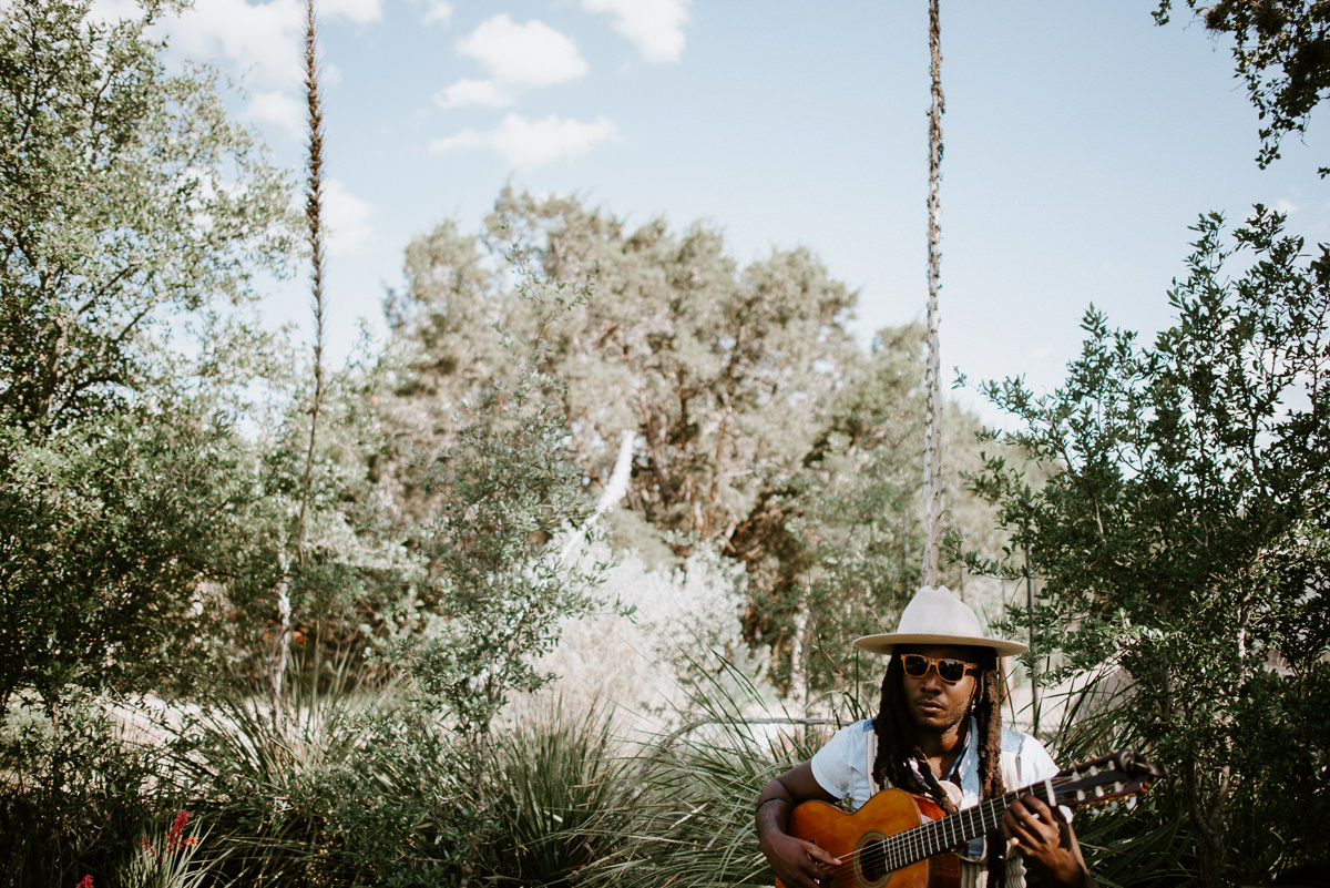 musician plays guitar for the greenhouse at driftwood wedding ceremony