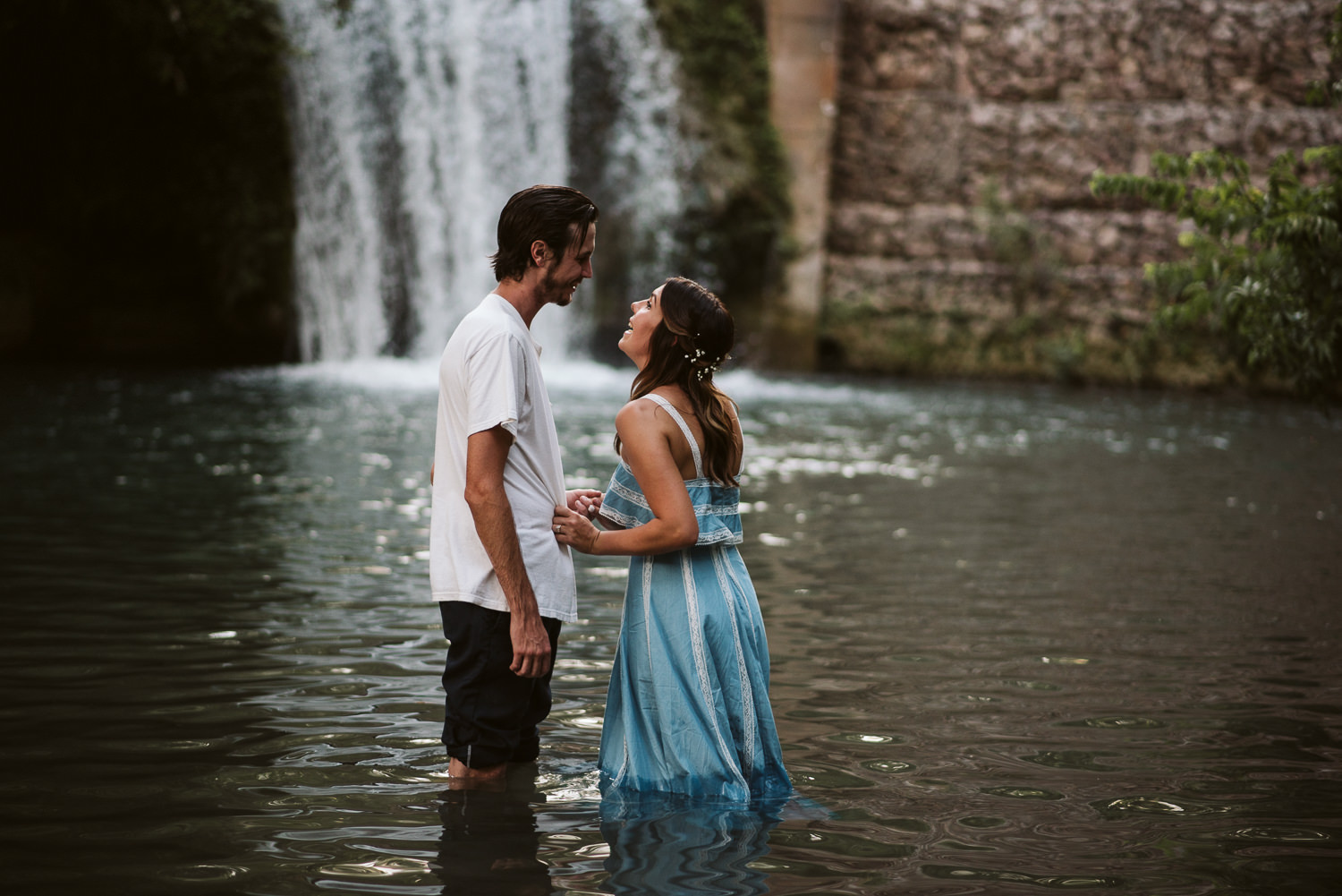 couple laughing in the river at engagement session