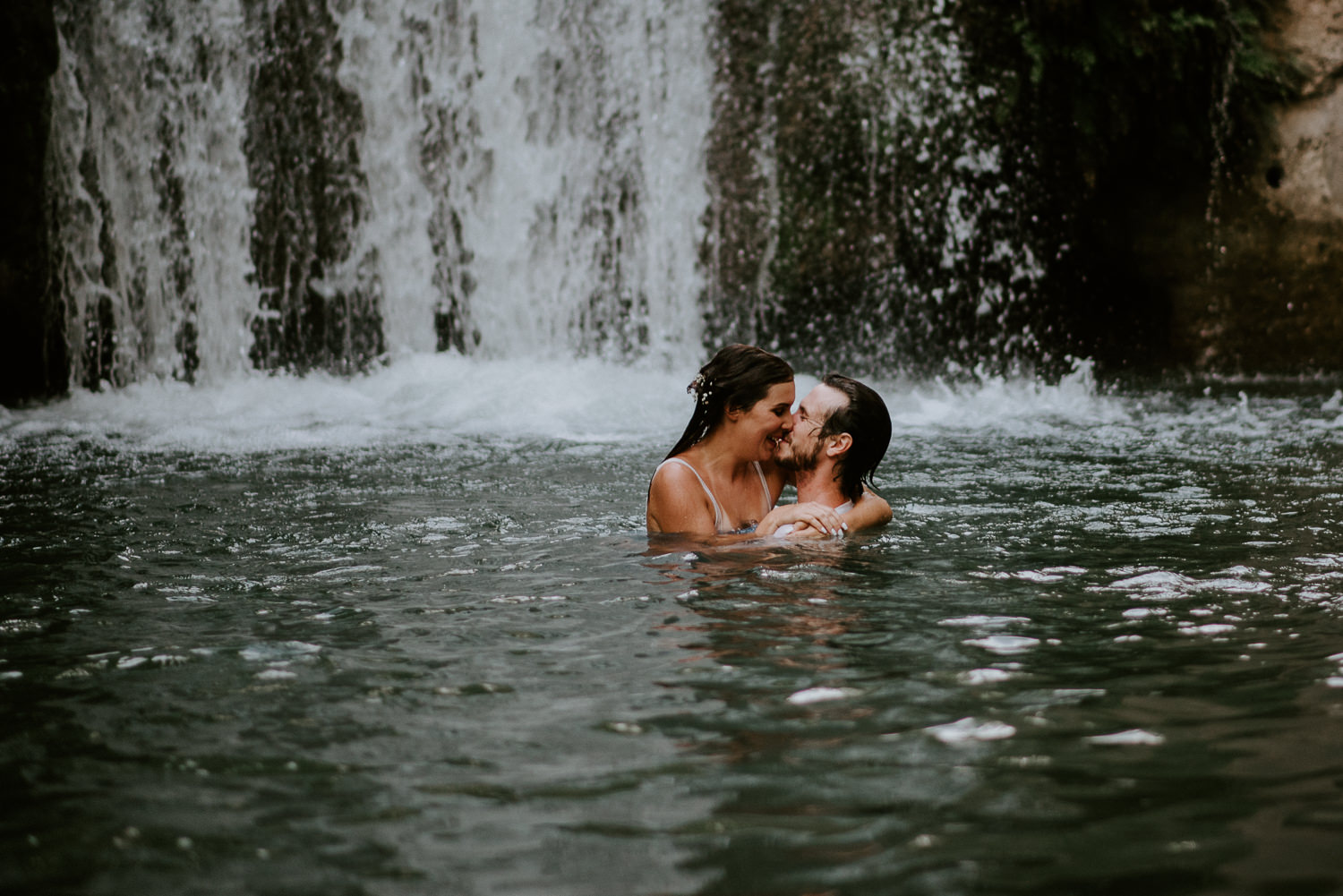 couple jumps in river at texas engagement session