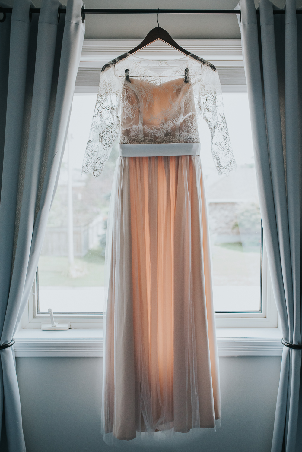 Blush wedding dress with off white lace overlay hanging in the window