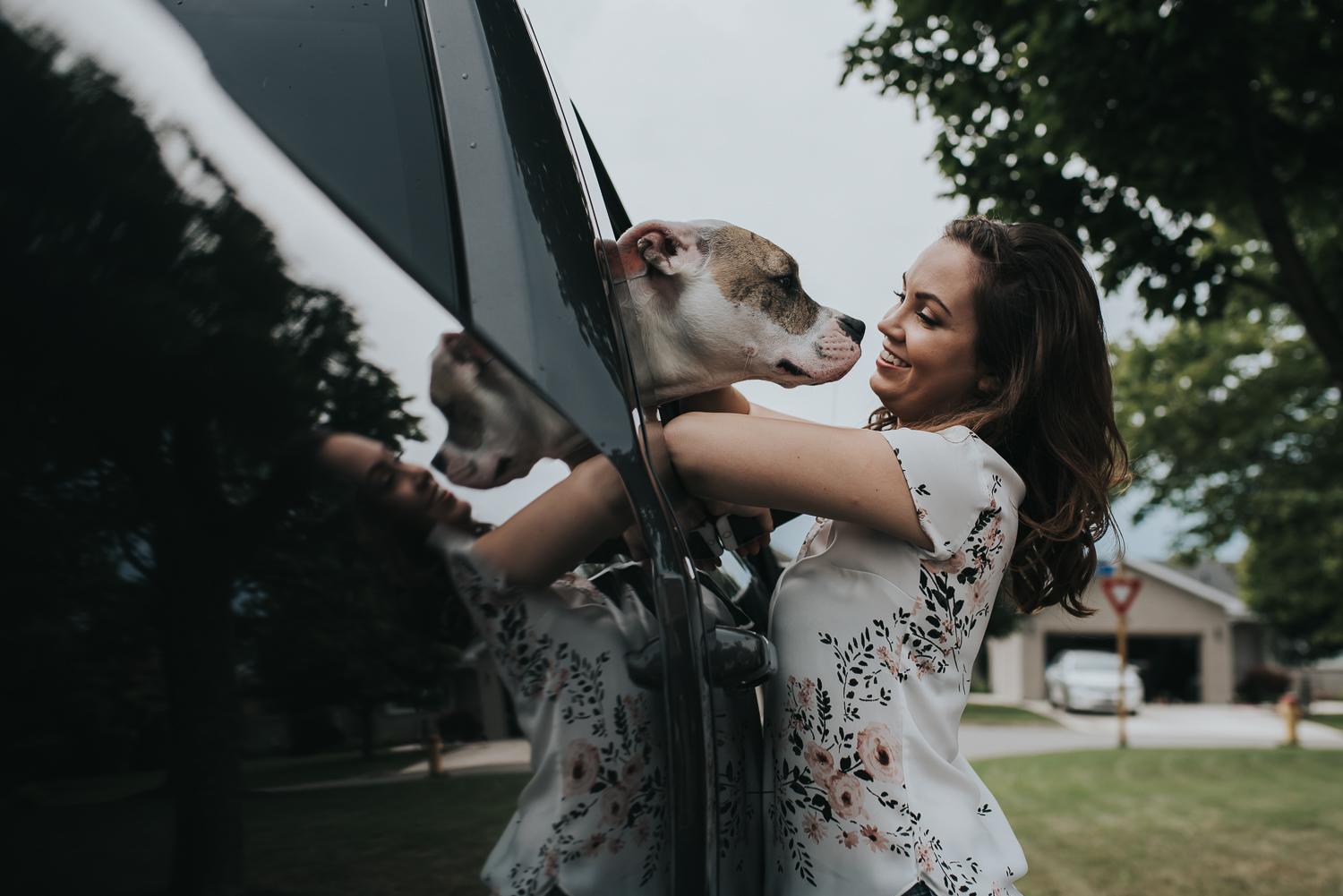 Bride being greeted by her dog out of black truck window