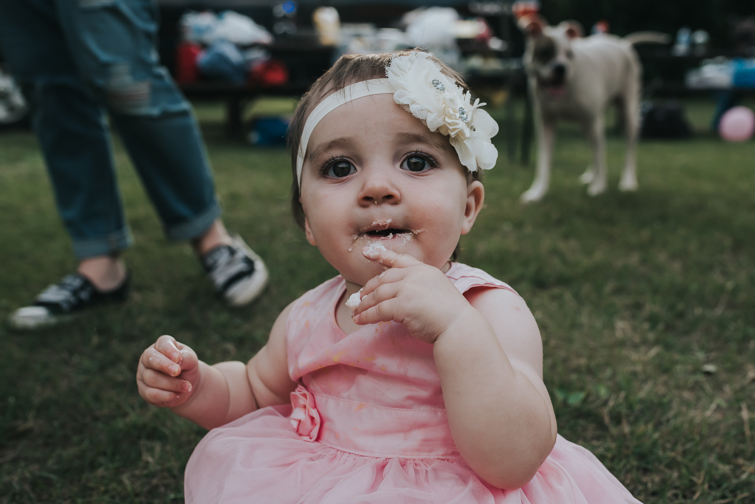 Baby girl in pink dress and white flowers in her hair with fingers and face covered in white icing sitting in the grass
