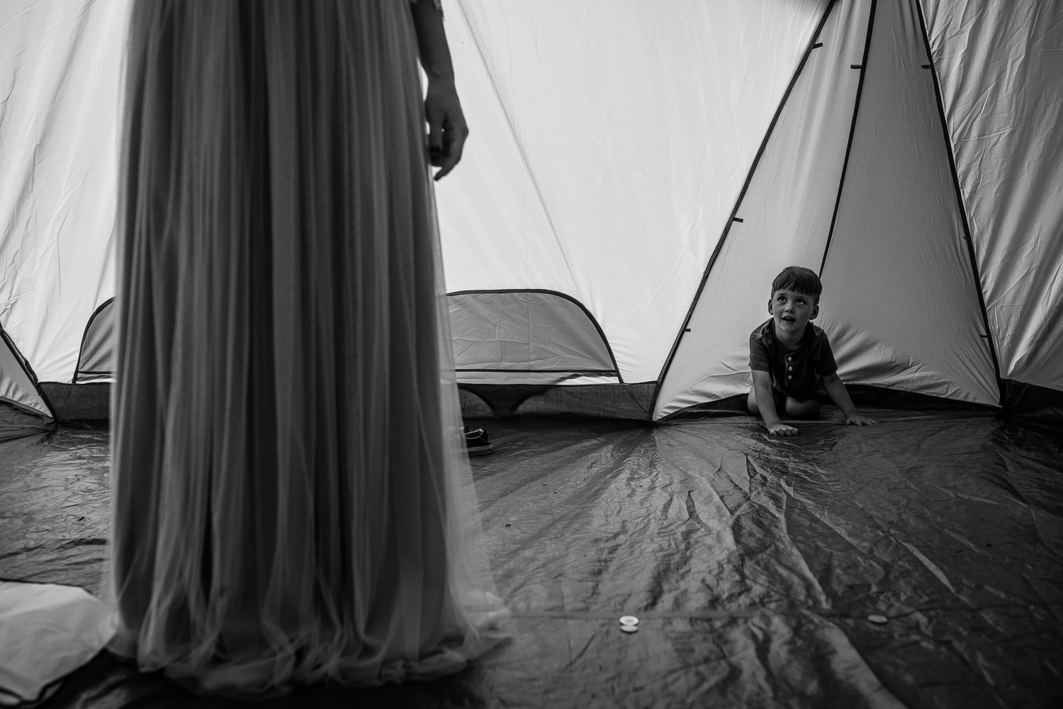 Mom getting into wedding dress as little boy watches from behind in a tent