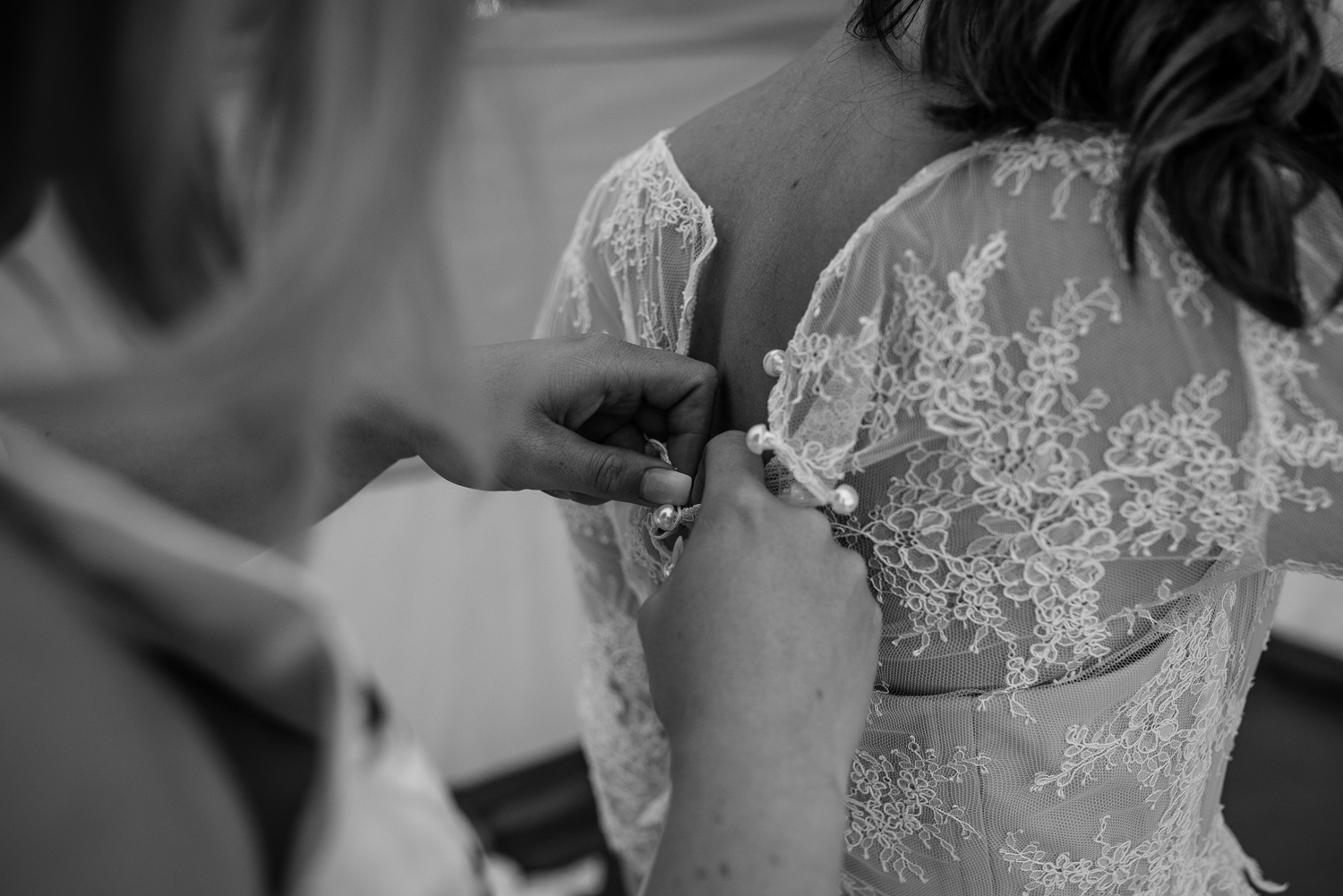 Bride getting into her wedding dress while bridesmaid helps fasten her back buttons