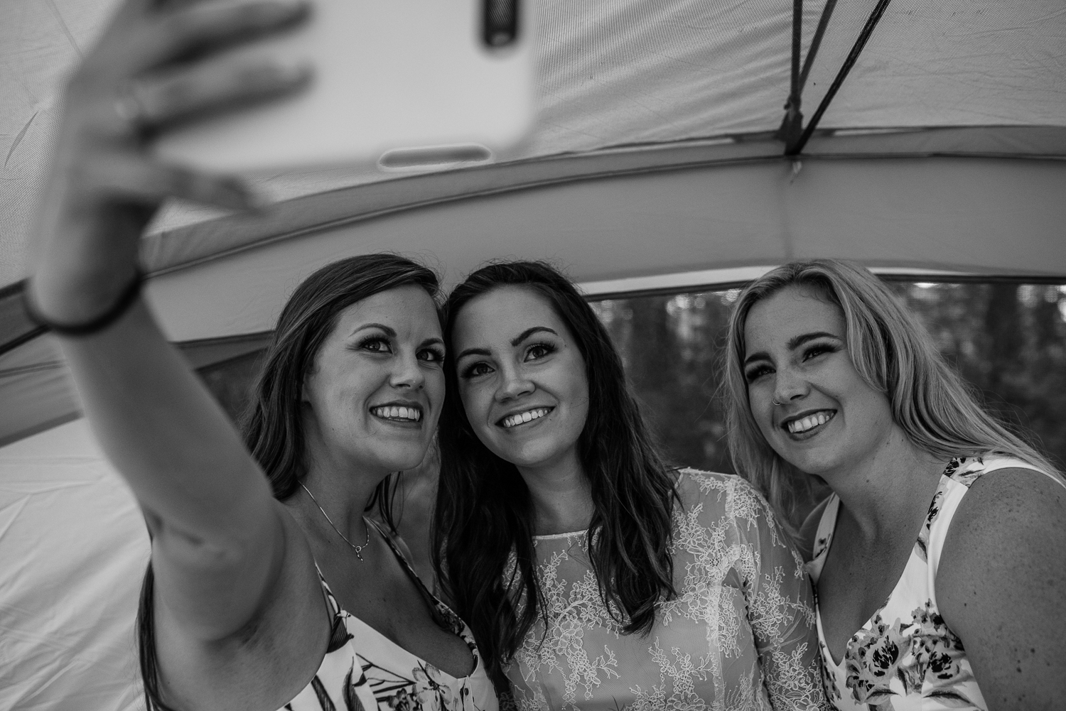 Bride and bridesmaids taking a selfie after getting into their dresses