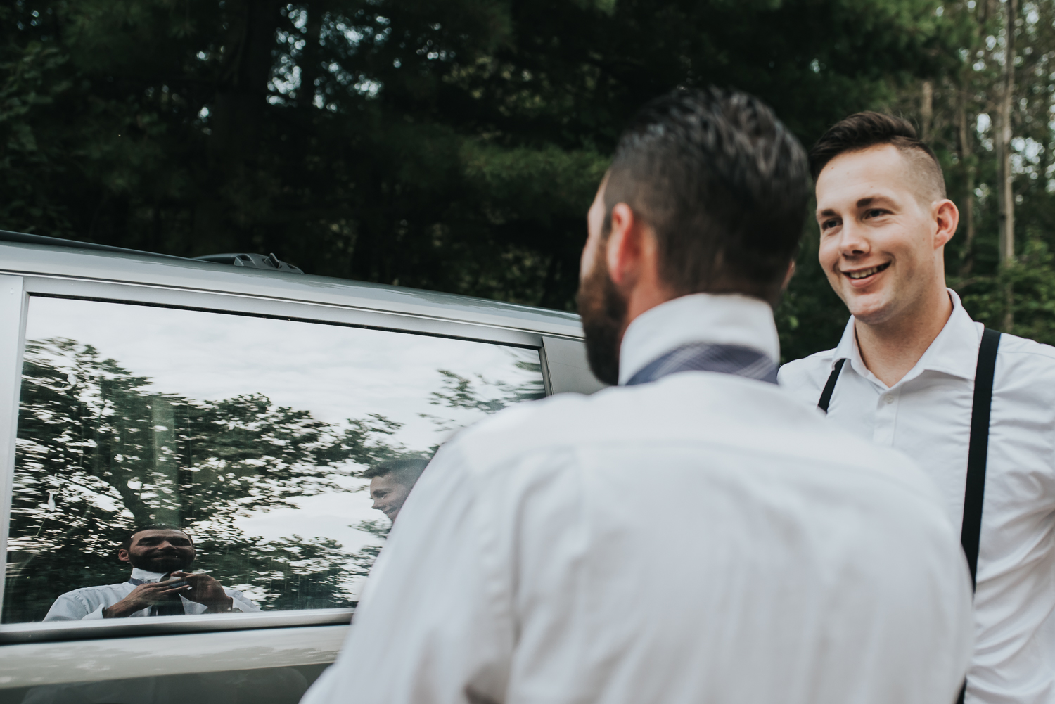 Groom putting on his tie in the reflection of a car window while his groomsman looks on both in white shirts and black suspenders