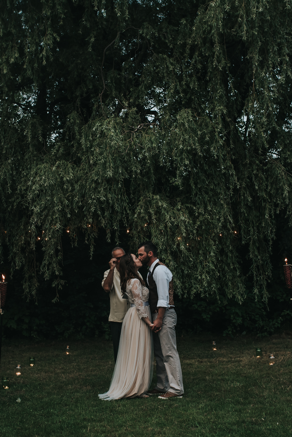 First kiss between the bride and groom surrounded by candles, twinkly lights and green grass and trees