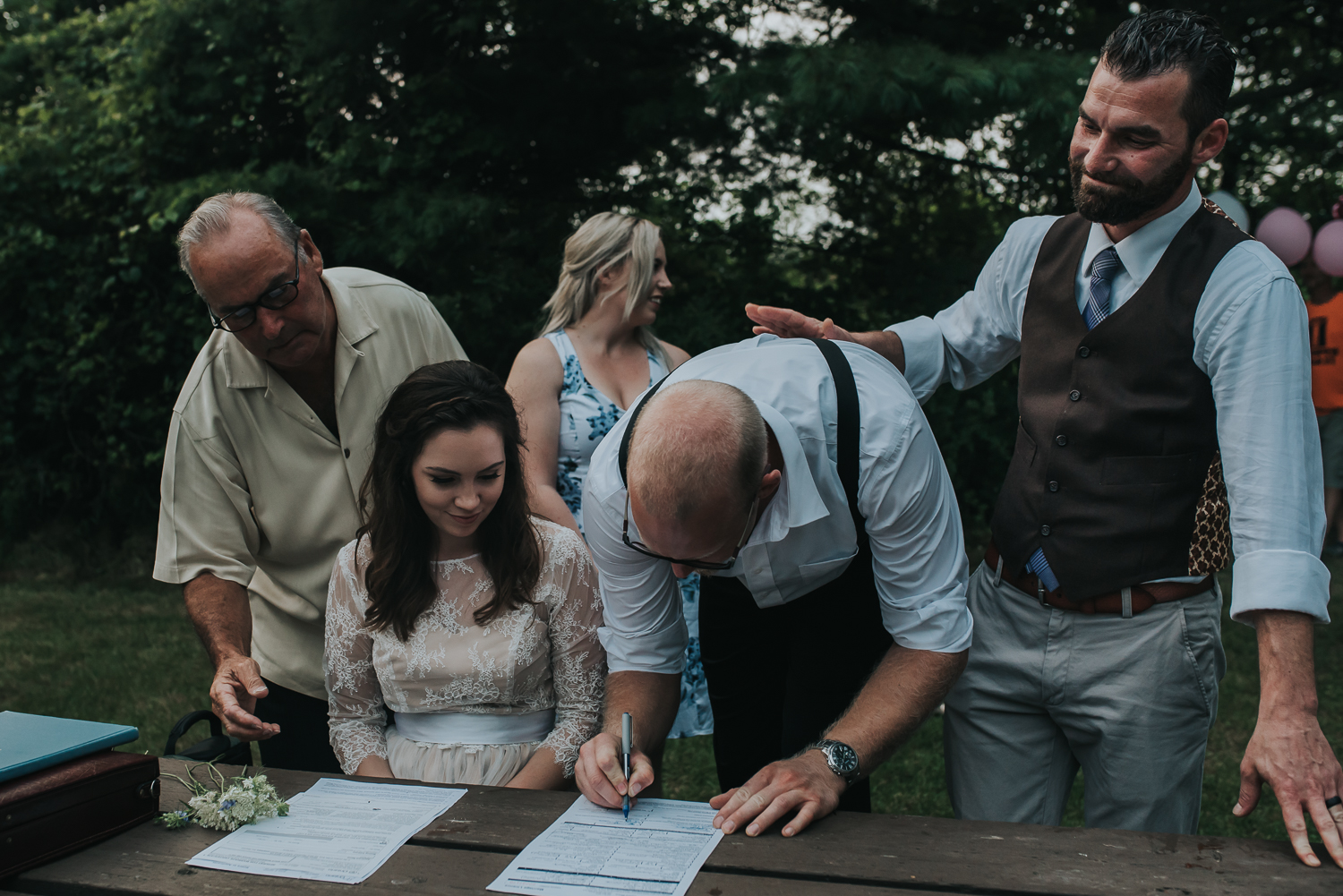 Bride and groom best man and bridesmaid sign the wedding registry licence on a picnic table