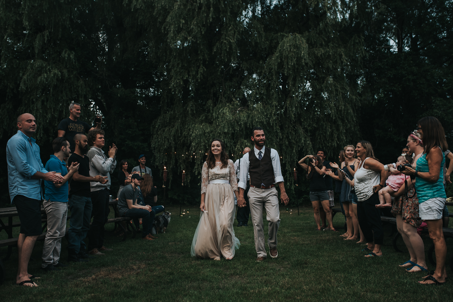 Bride in a blush and lace dress groom in beige pants brown vest and white shirt walk down the aisle surrounded by family friends trees and twinkly lights