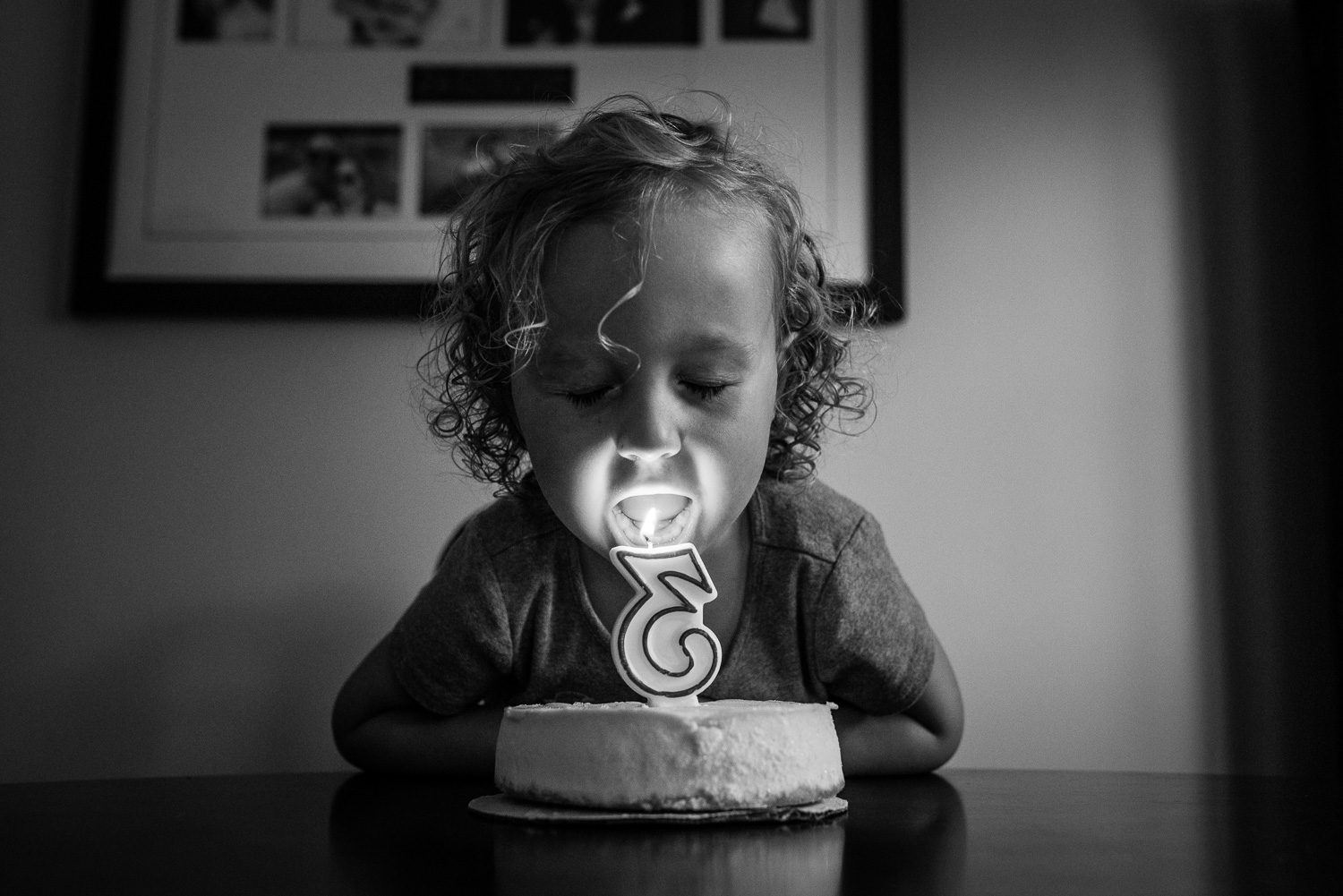 Toddler girl with curly hair at a table blowing out a number three candle on a small white cheesecake with photographs on the wall in behind her.