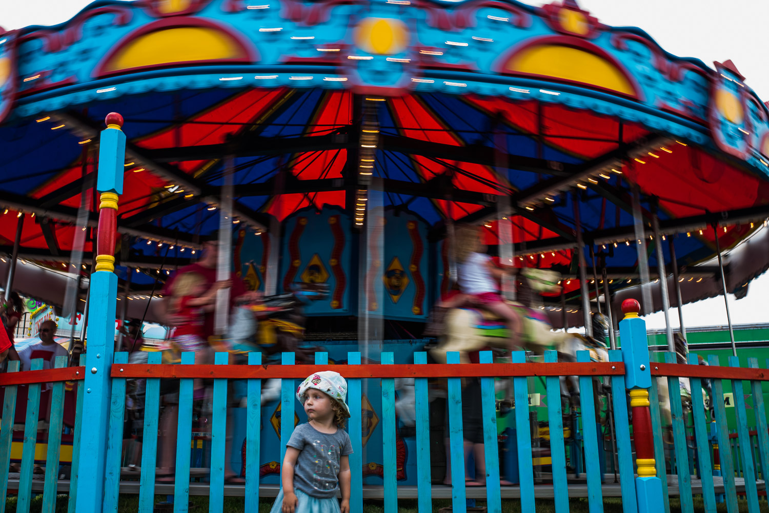 Toddler girl in grey t-shirt and blue tule skirt in front of colourful carousel which is spinning